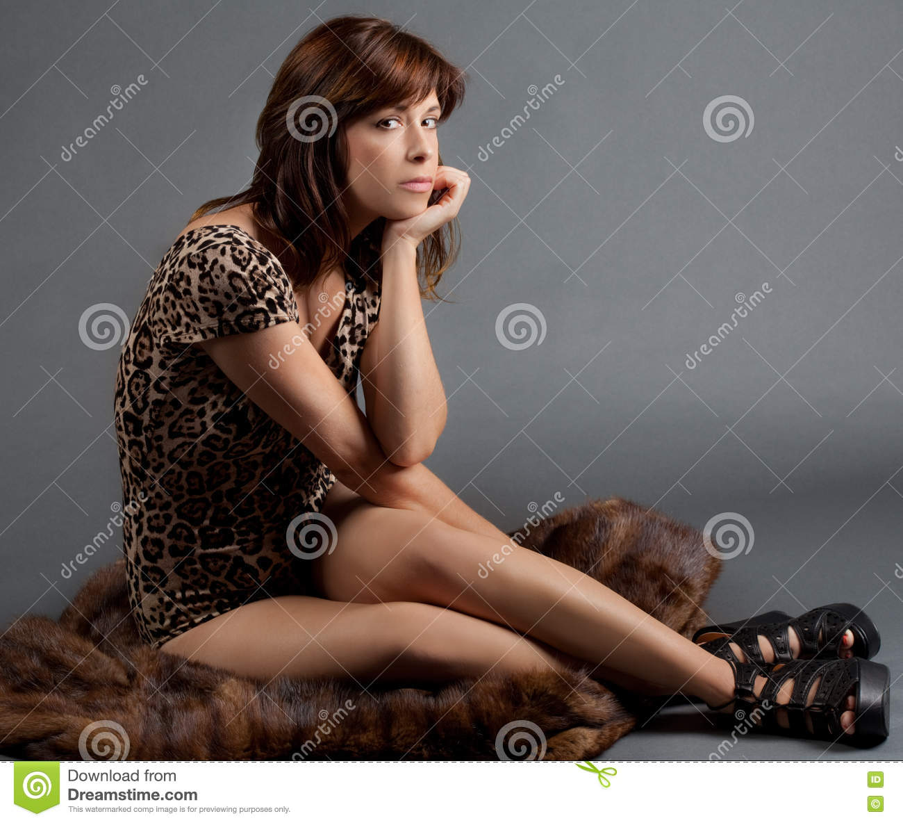 a4fcb9b041a7 An image of a young woman in a leopard print leotard sitting on fur and  looking bored