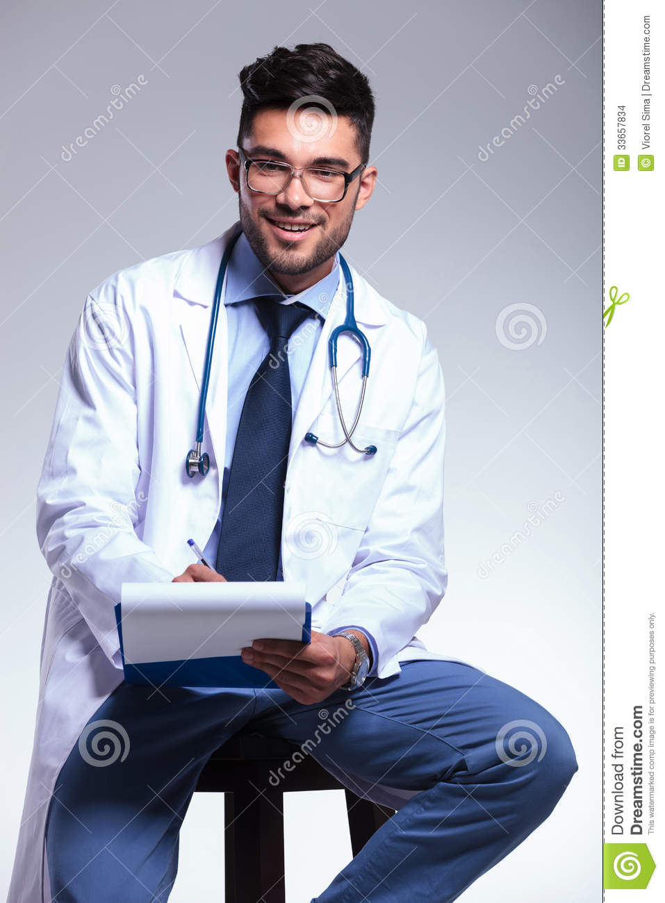 Seated Young Doctor Writing On Clipboard Stock Images