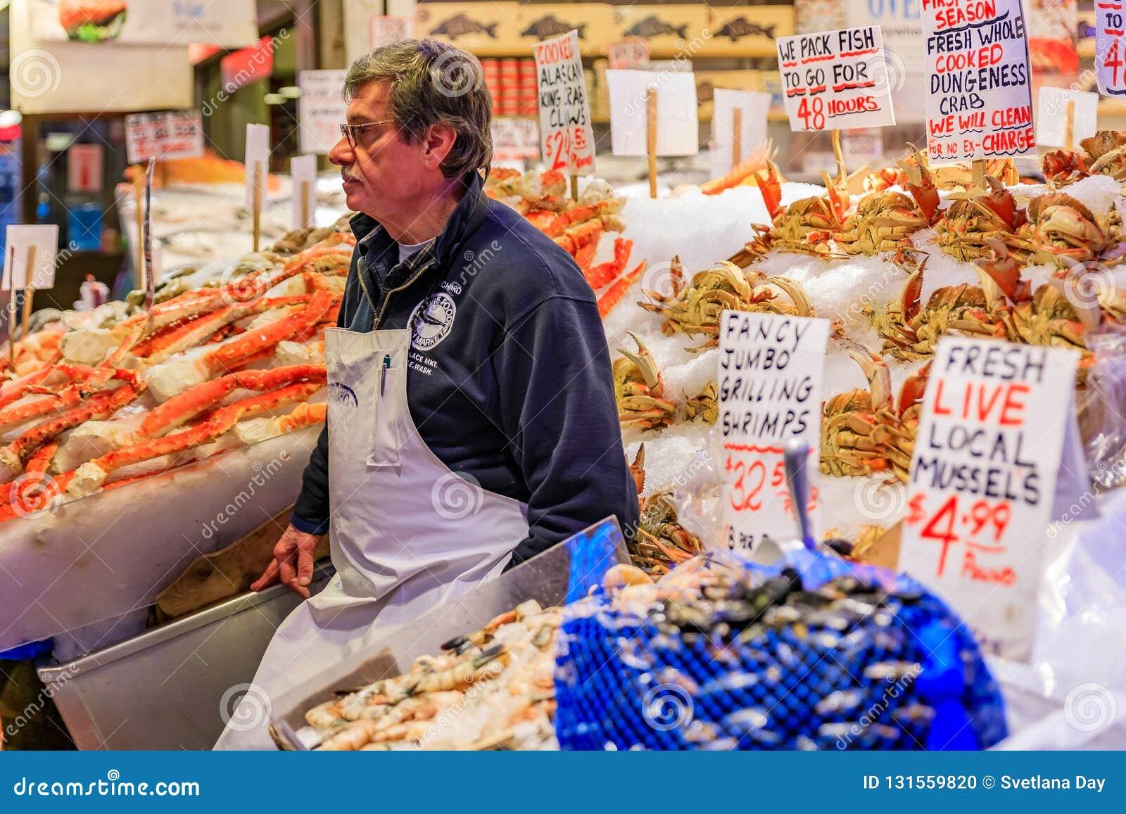 Seattle, Vereinigte Staaten - November-Fischhändler an einem Stall mit frischen Meeresfrüchten wie Krabbe, Garnele und Miesmusche
