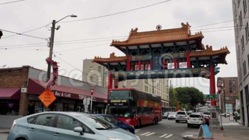 Seattle historic Chinatown Gate on an overcast day with traffic and  onlookers