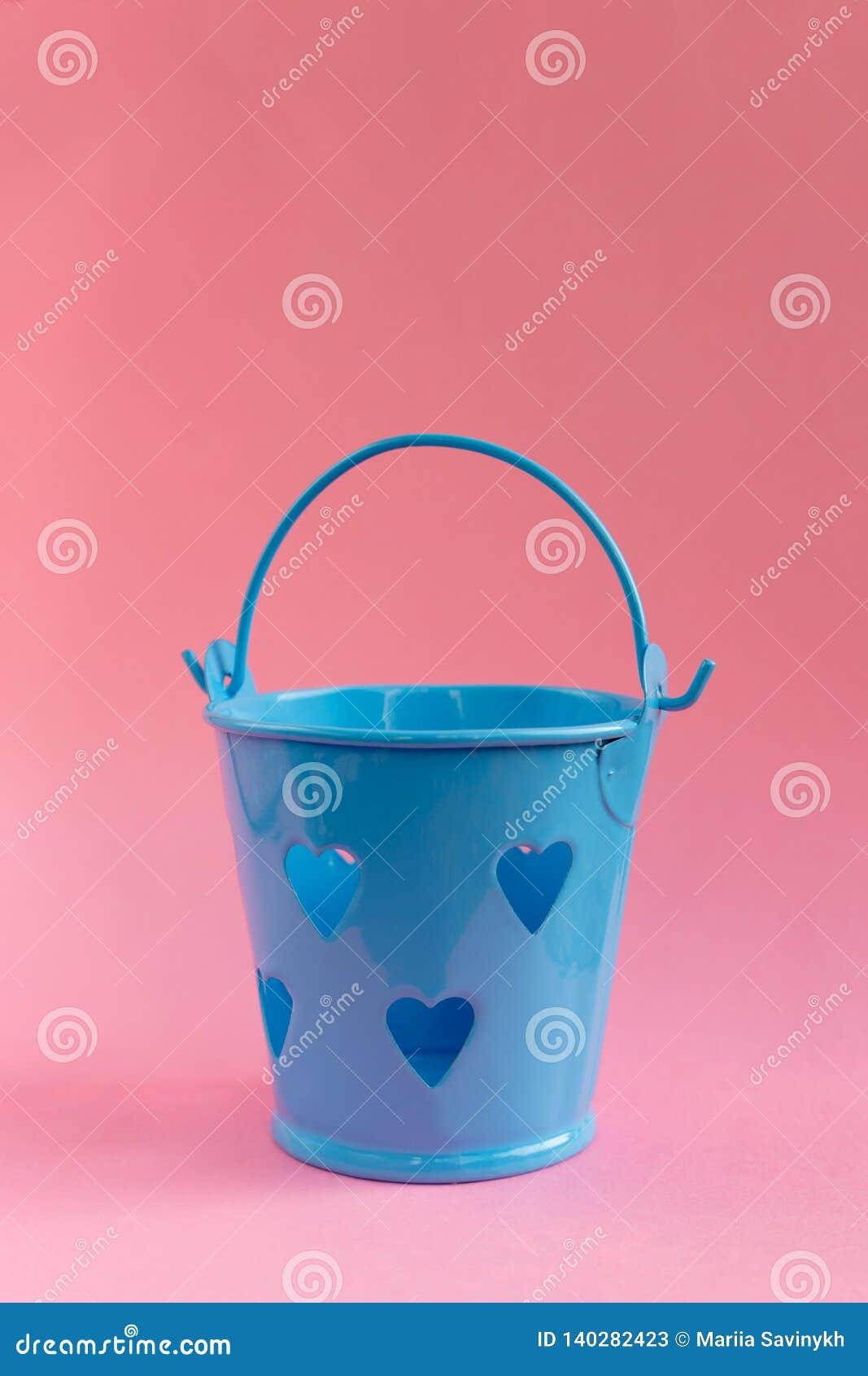 Seau bleu décoratif avec les trous en forme de coeur sur le fond rose Concept de fête