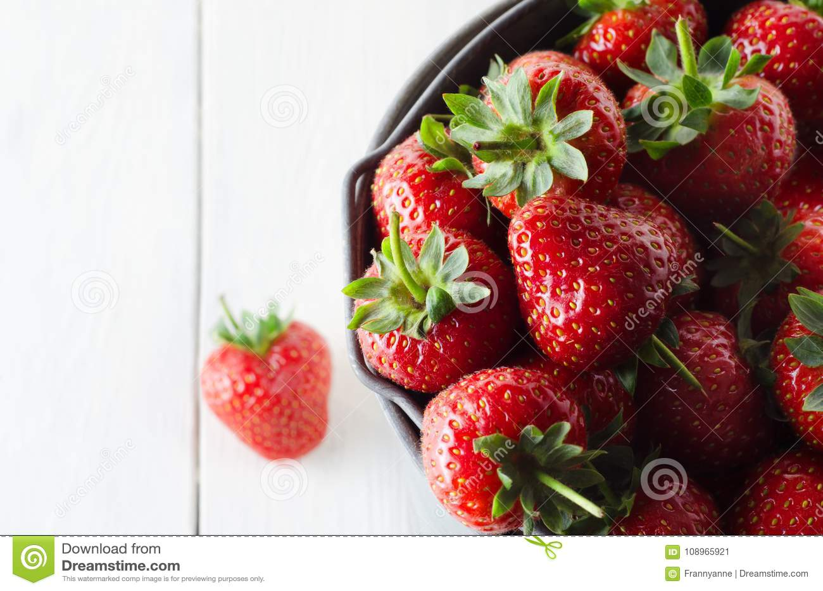Seau rempli de fraises sur le Tableau en bois blanc de Planked