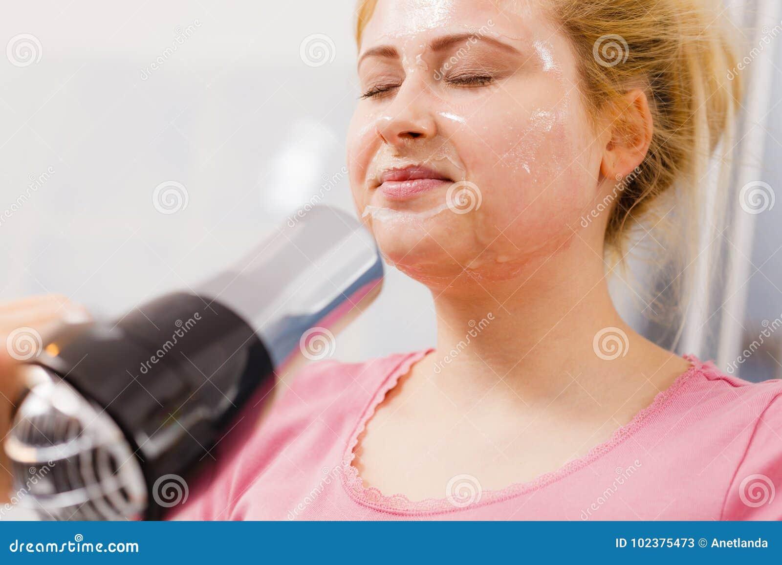 A secagem da mulher sua descasca fora o secador de cabelo da máscara protetora