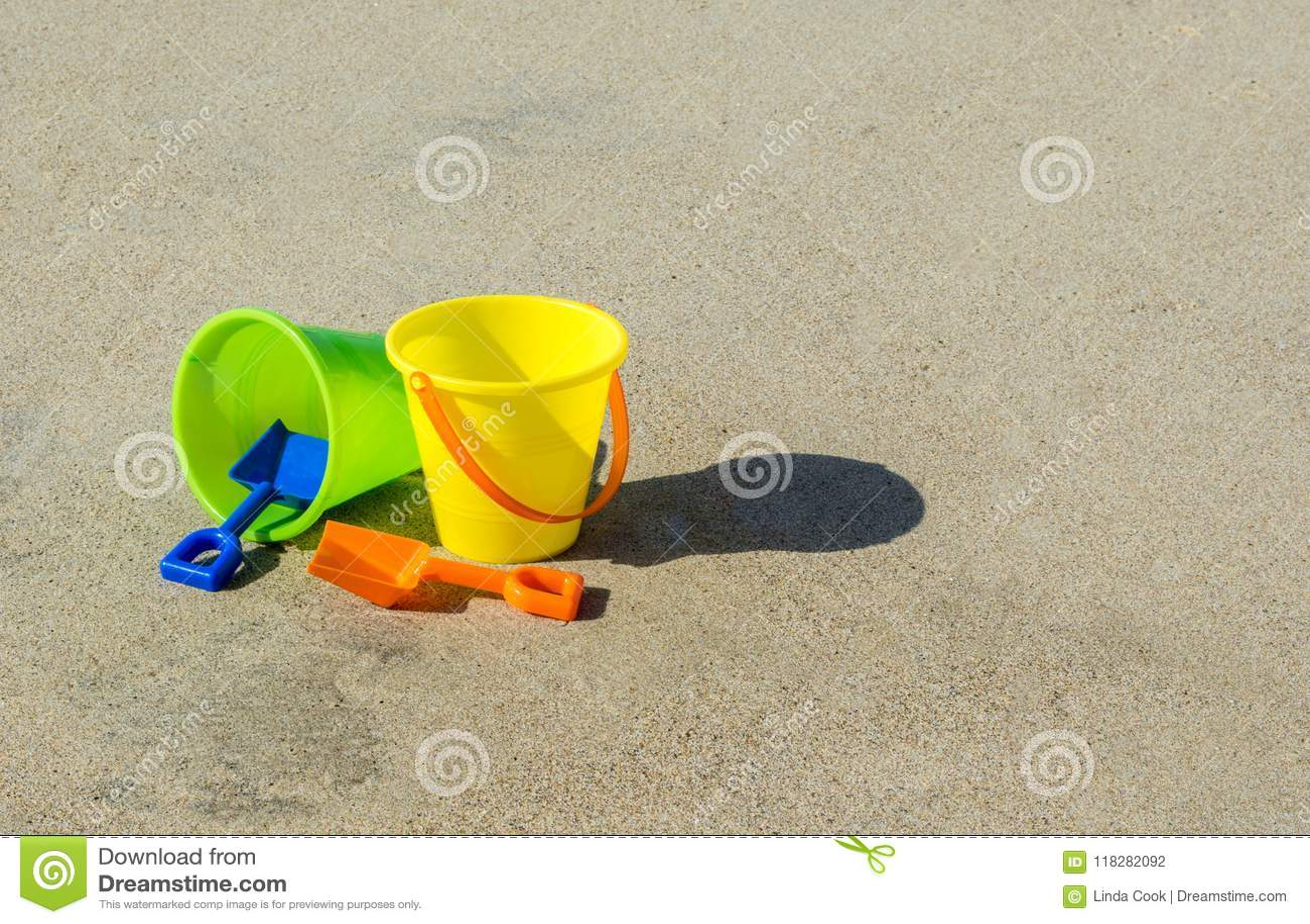 2 secchi e pale di plastica della sabbia su una spiaggia sabbiosa liscia