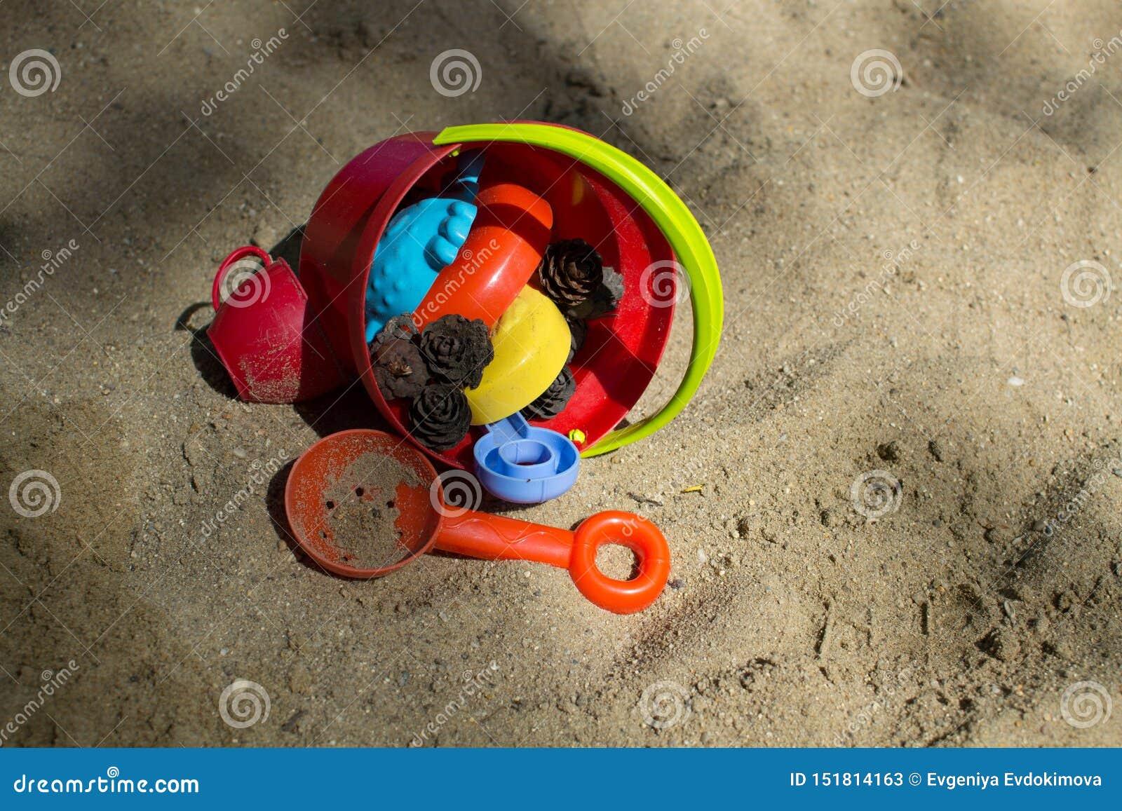 Secchio rosso con i giocattoli dei bambini sulla sabbia