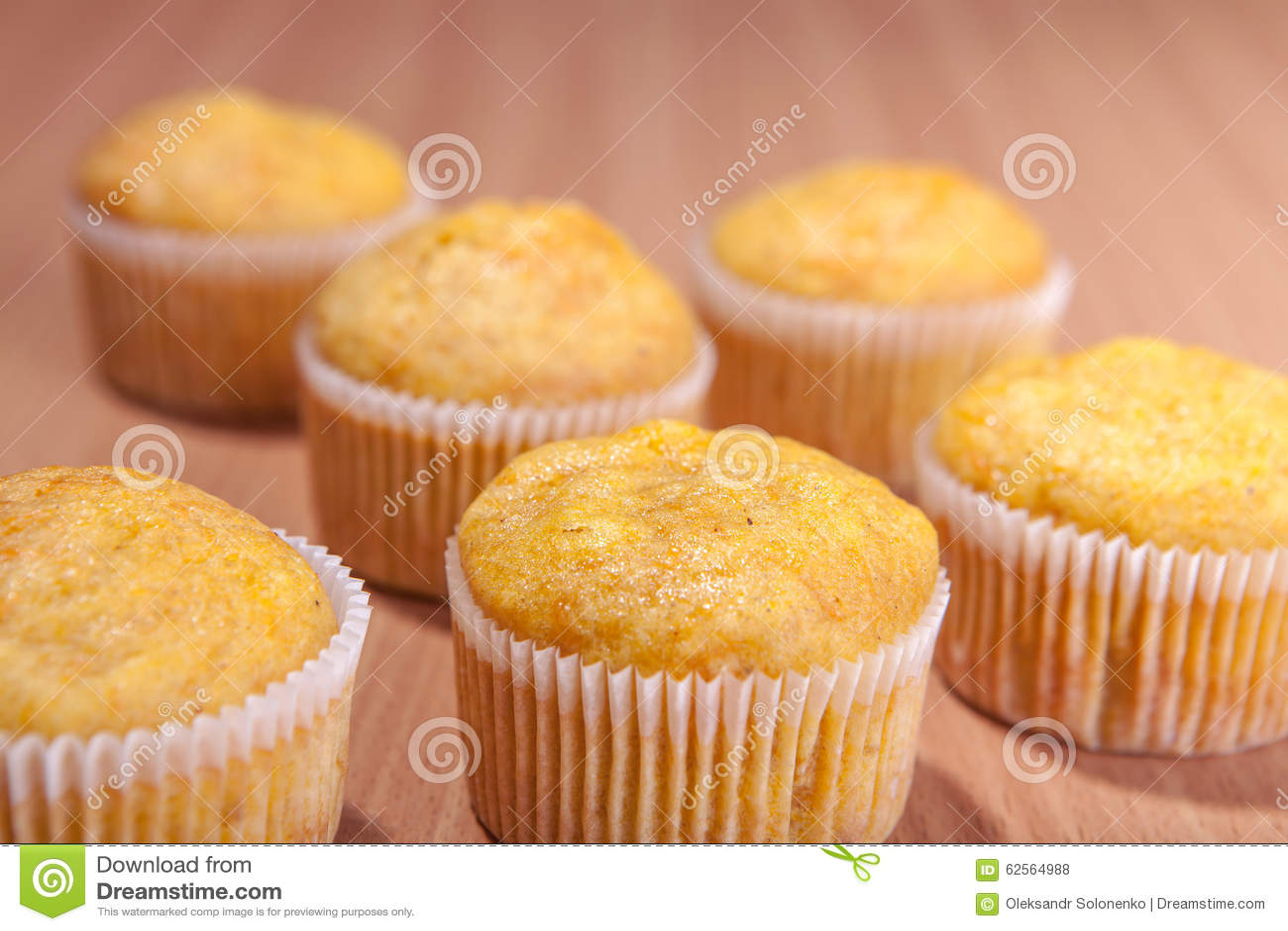 Sechs kleine Kuchen auf hölzerner Beschaffenheitstabelle