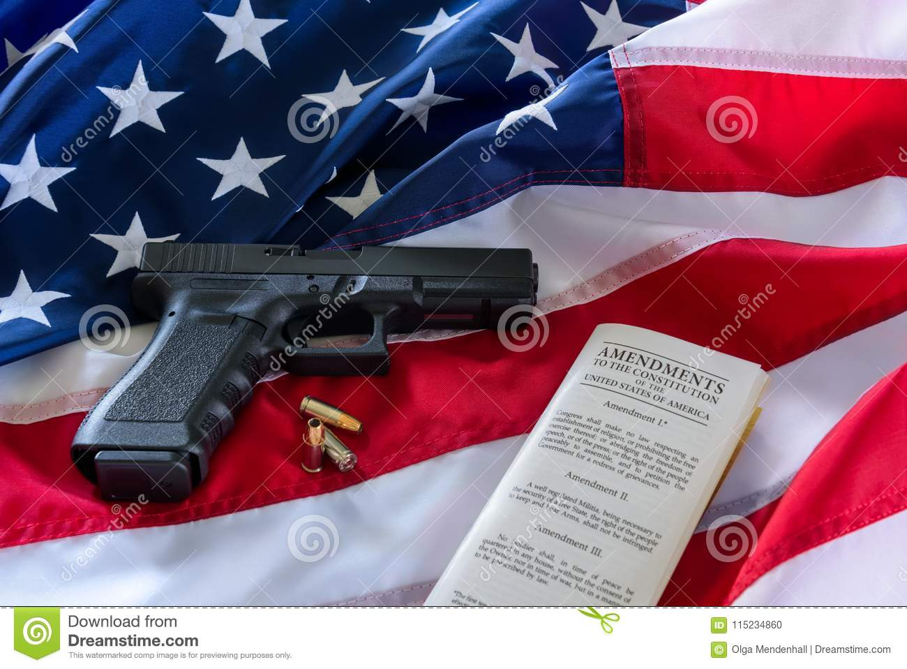 The second amendment and gun control in the US, concept. Handgun, bullets, and the american constitution on the USA flag
