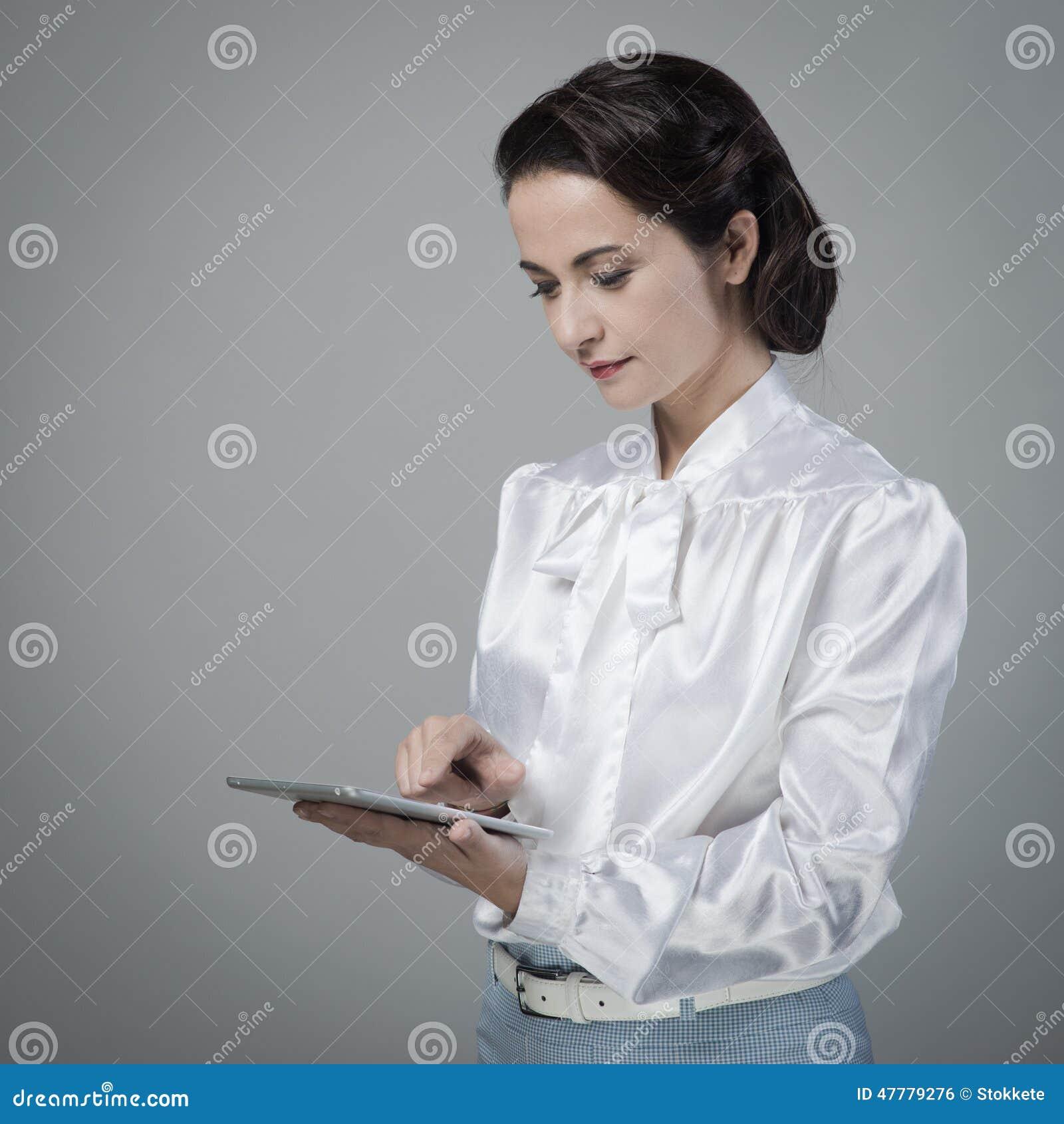 Secretaria del vintage que usa la tableta