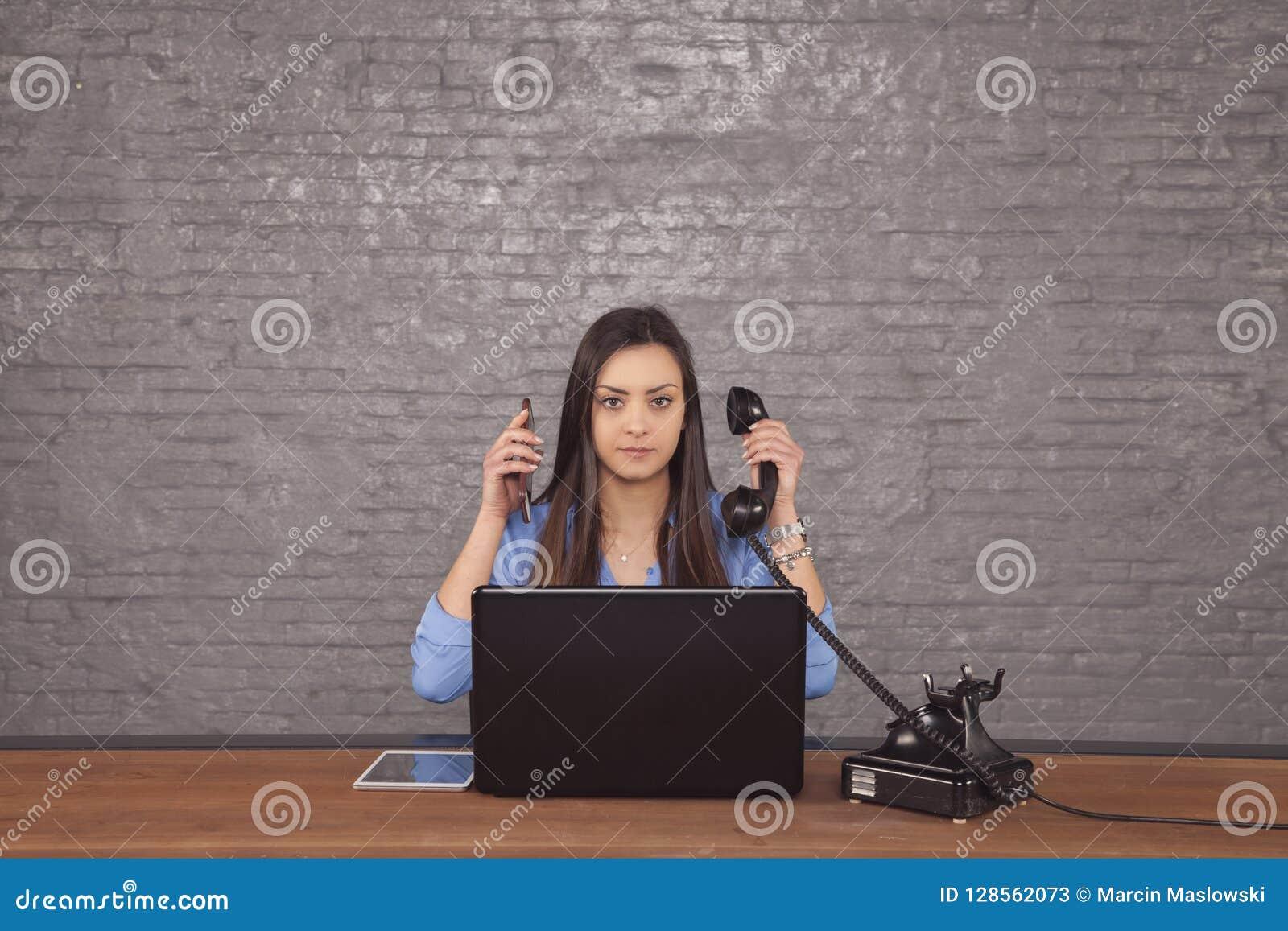 Secretaria hermosa joven para conducir dos llamadas de teléfono al mismo tiempo
