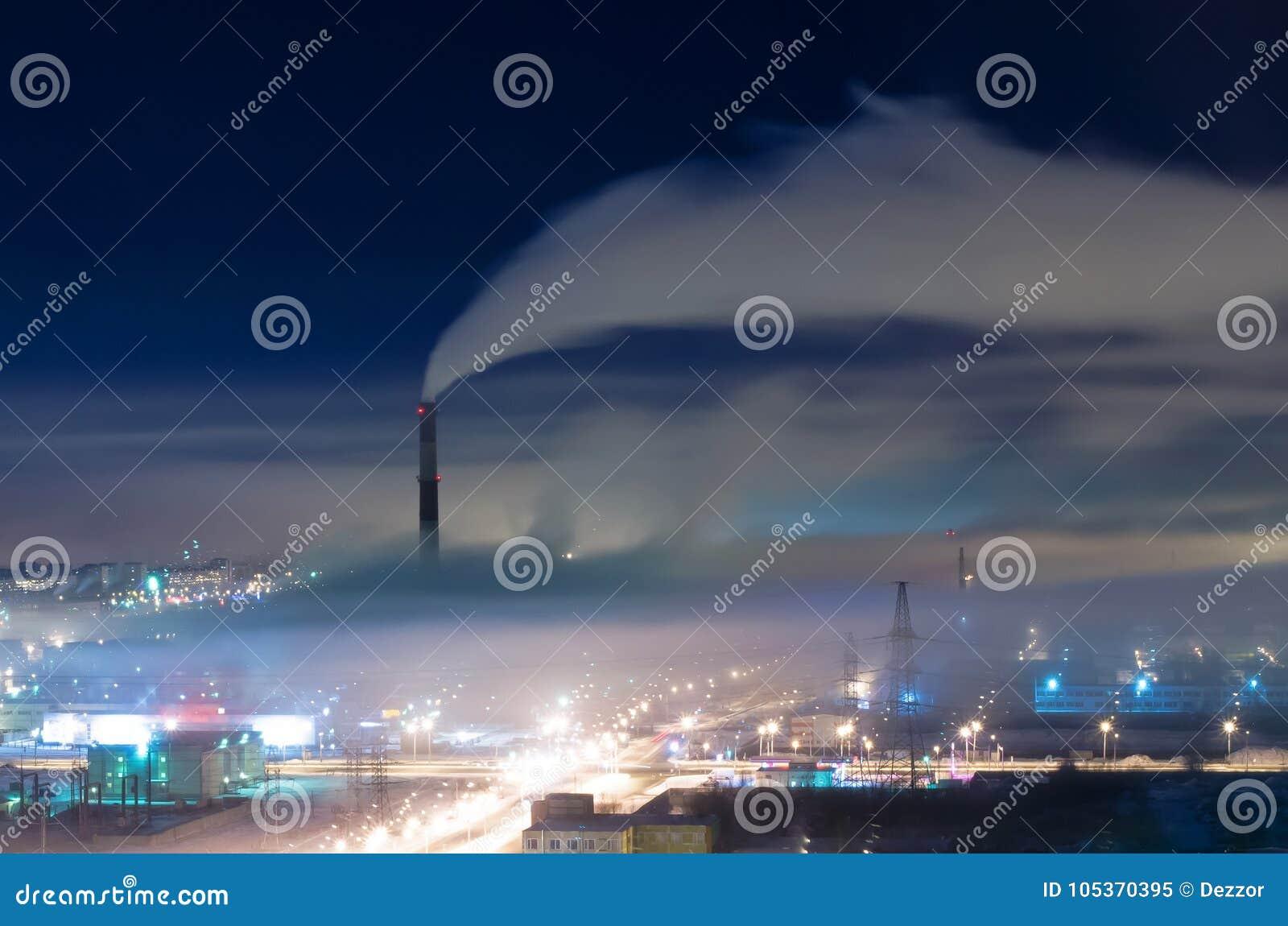 Secteur industriel de la ville, des tuyaux et de la fumée, avec le brouillard et le brouillard enfumé la nuit
