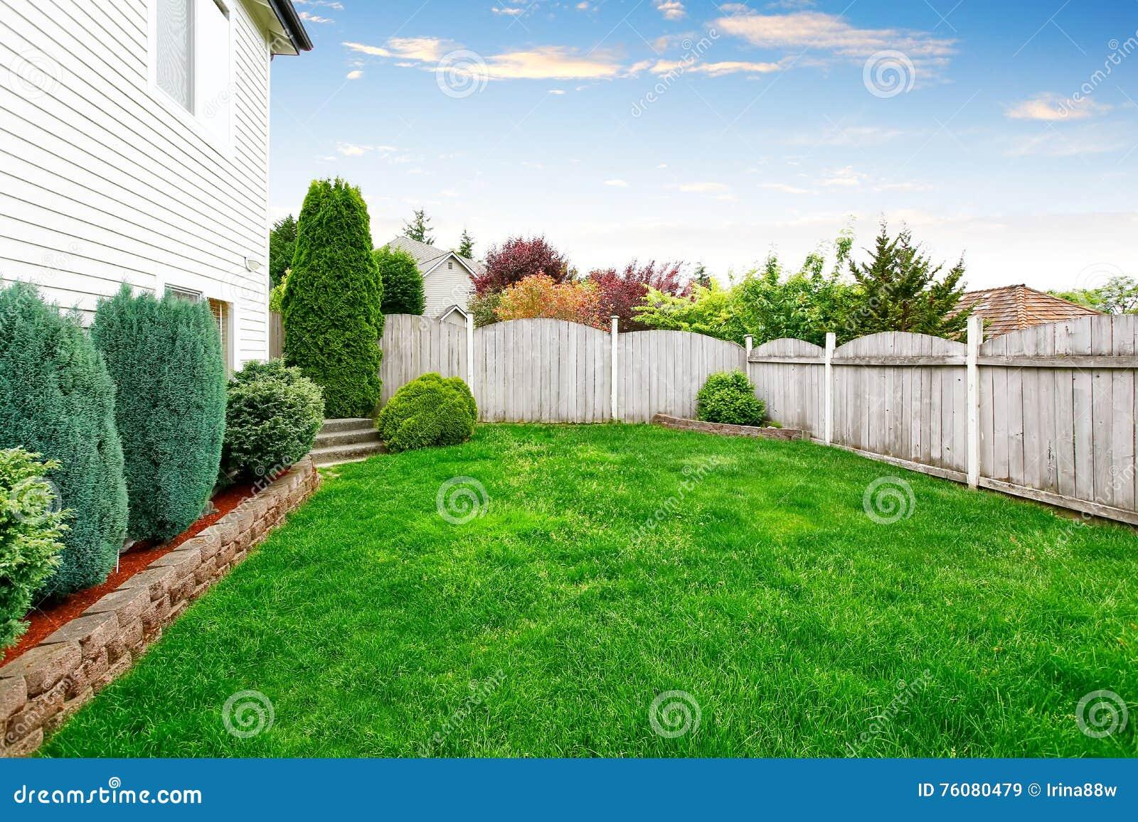 Secteur spacieux d arrière-cour avec la barrière en bois et la pelouse soignée