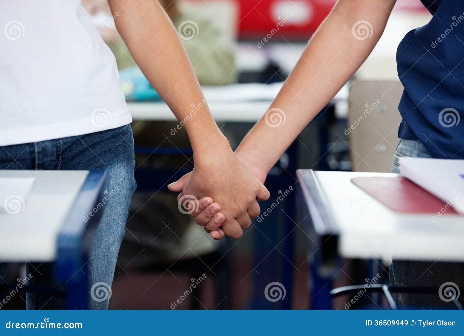 Section médiane de l écolier et de la fille tenant des mains à