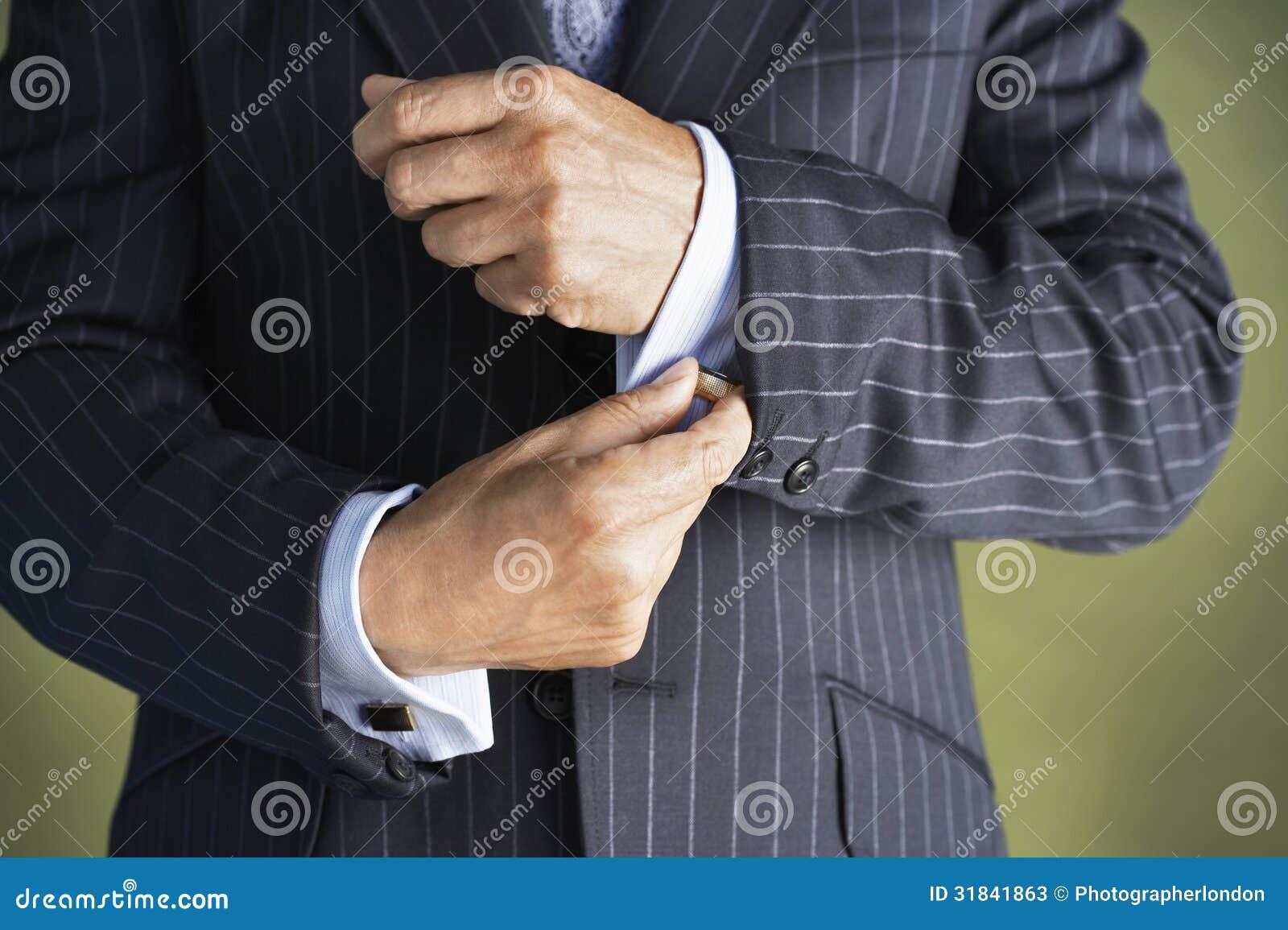 Section médiane de l homme dans le costume boutonnant des douilles de manchette