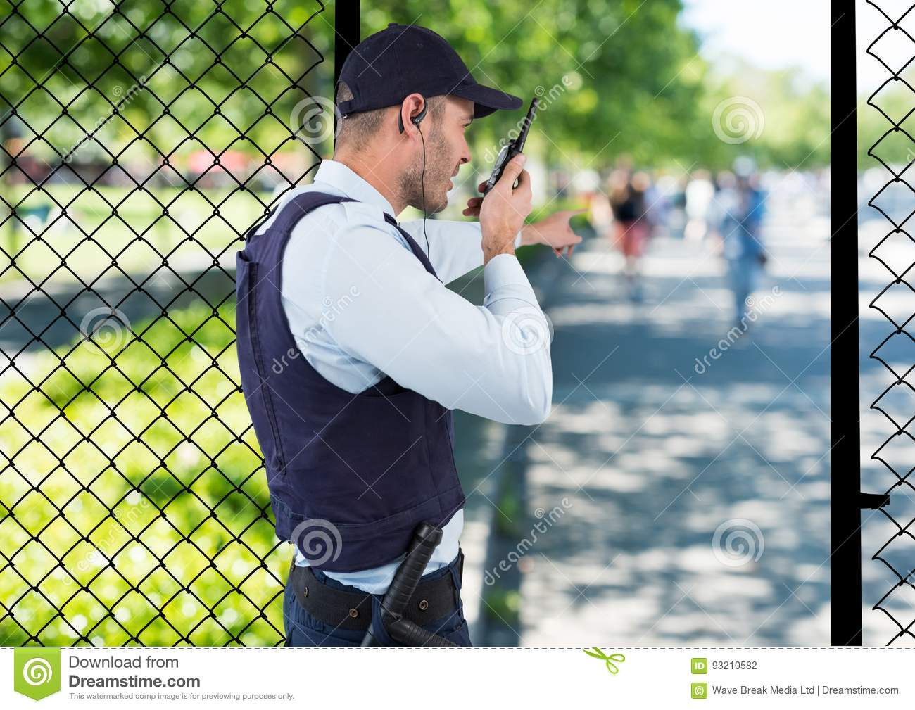 security guard of the park spiking with the walkie-talkie and point to something.