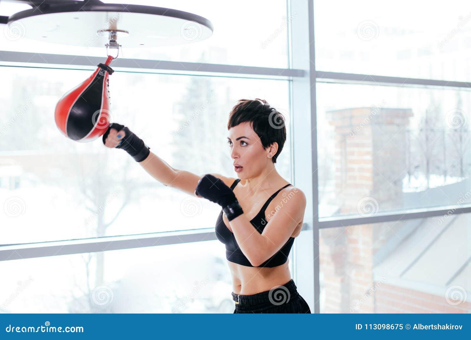 Sede widoku strzał przyjemna kobieta w czarnym sportswear rozdaje cios