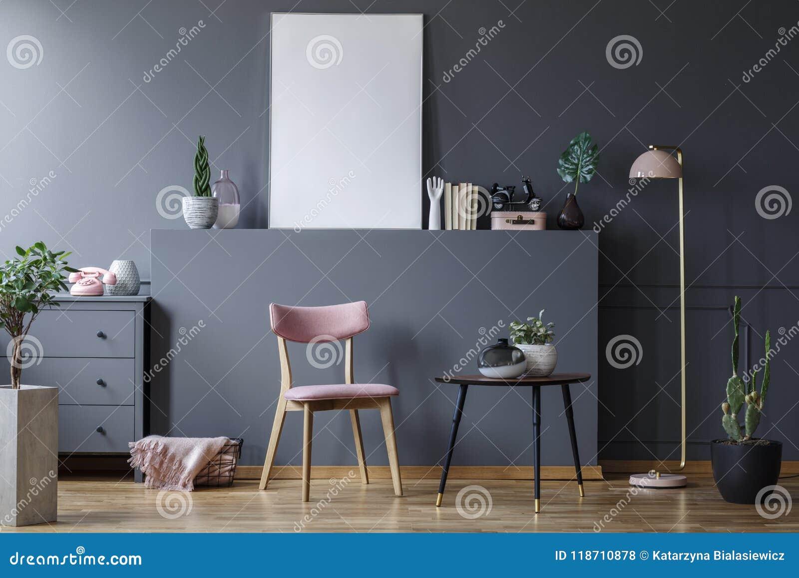 Sedia di legno rosa alla tavola nera nell interno grigio del salone con il modello del manifesto vuoto
