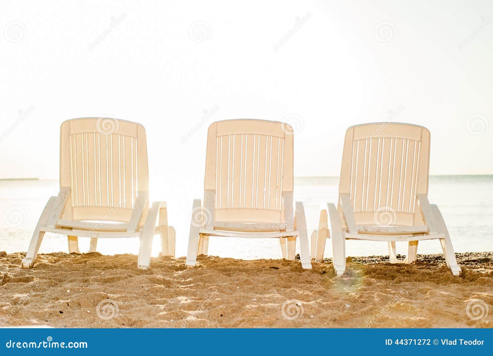 Sedia di spiaggia tre sulla spiaggia di sabbia