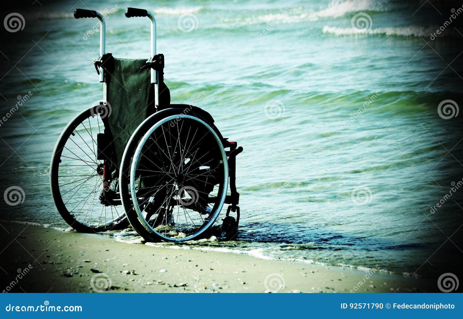 Sedia a rotelle sulla riva dal mare su uno spirito soleggiato caldo di giorno di estate
