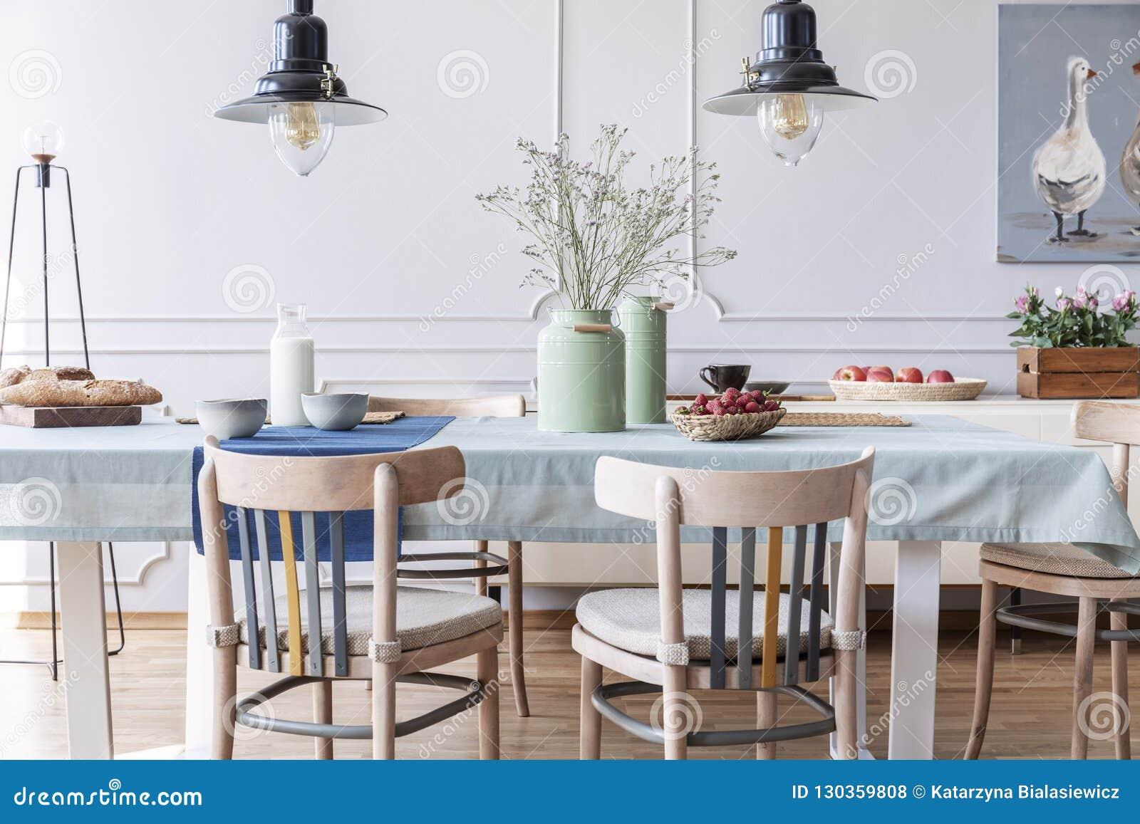 Sedie di legno alla tavola con i fiori e l alimento nell interno bianco della sala da pranzo del cottage con le lampade ed il man
