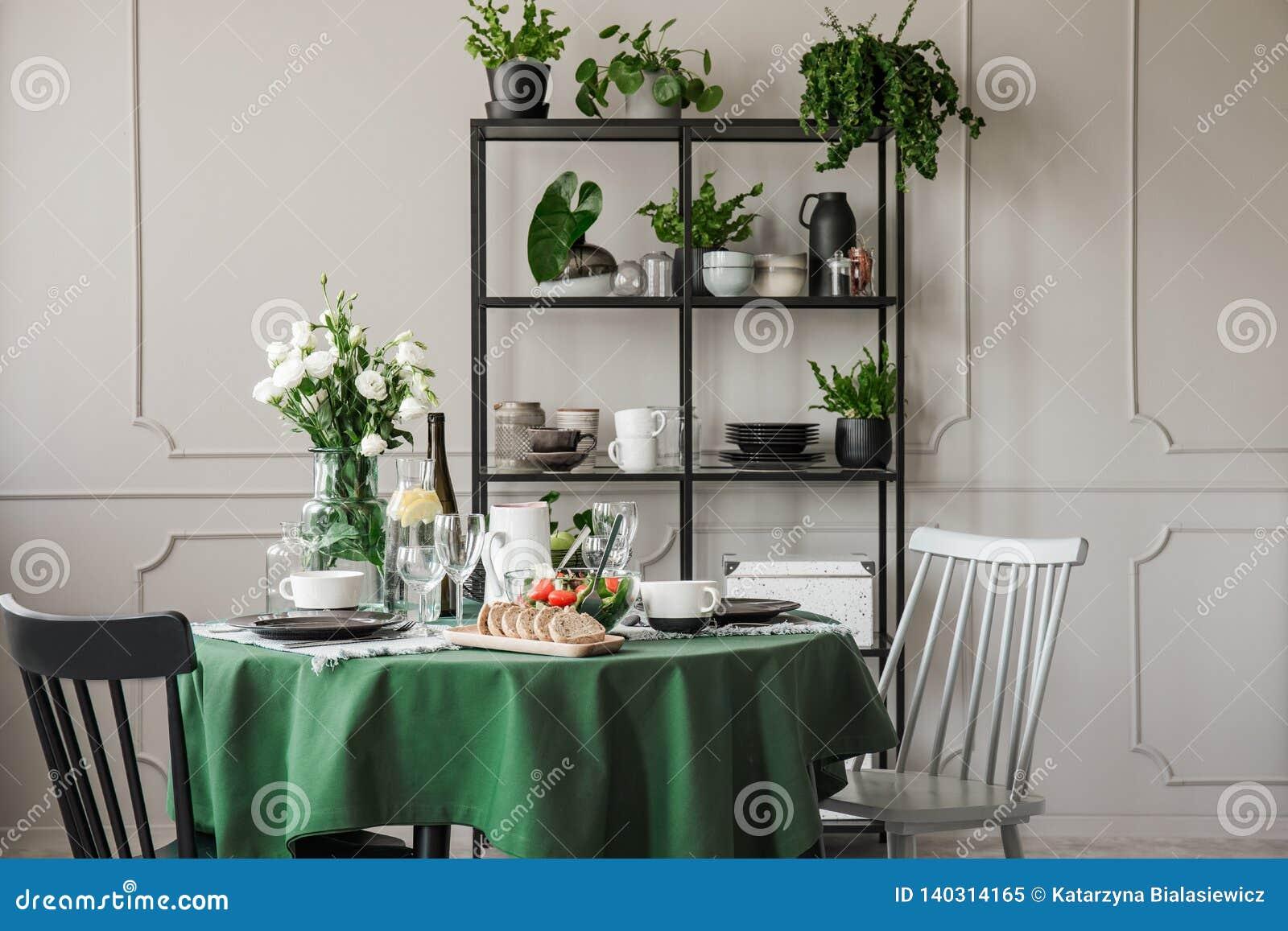 Sedie di legno grige e nere alla tavola rotonda con la tovaglia, i piatti, le tazze ed i vetri di vino verdi
