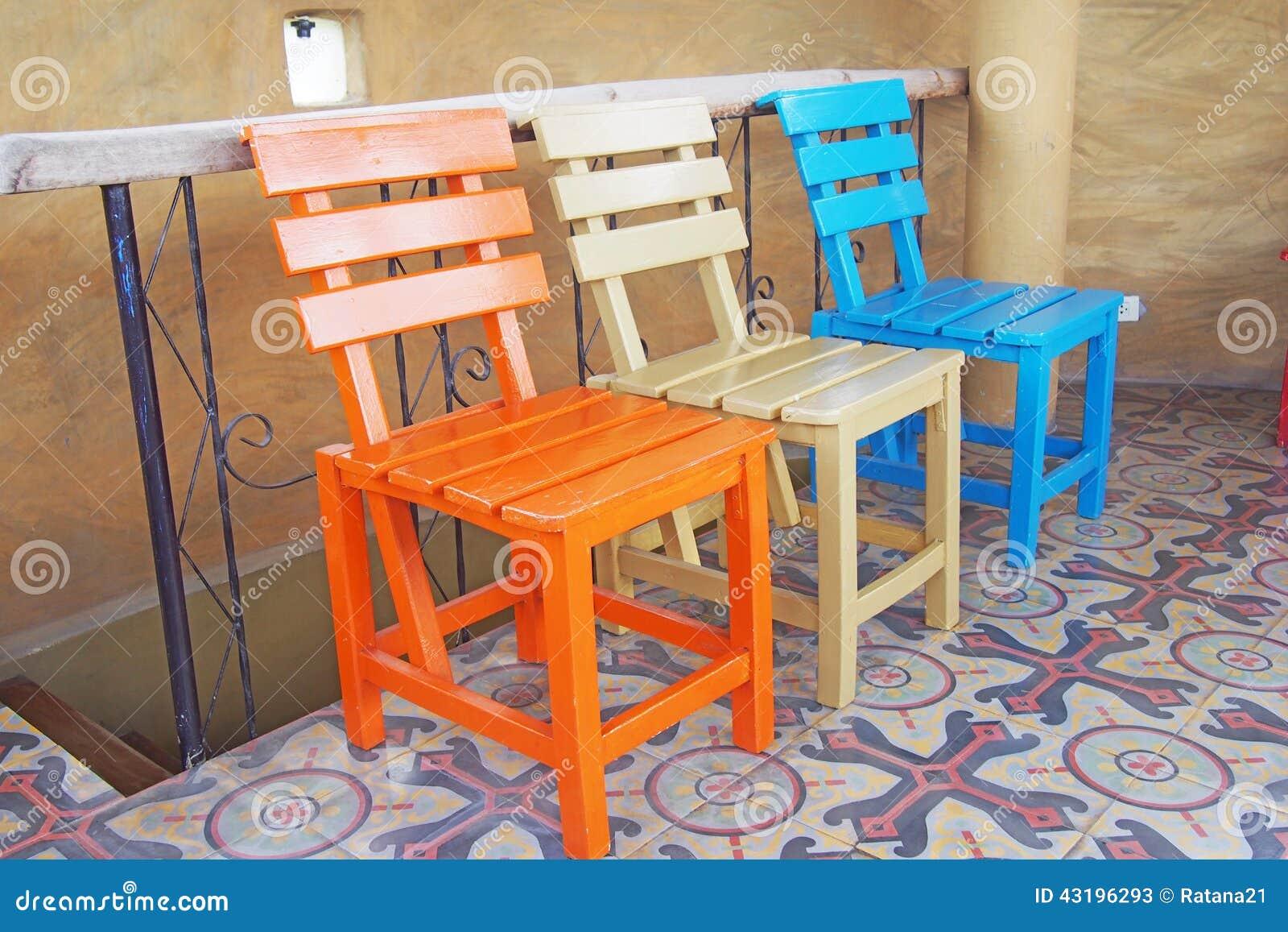 Sedie di legno sul pavimento delle piastrelle di ceramica immagine