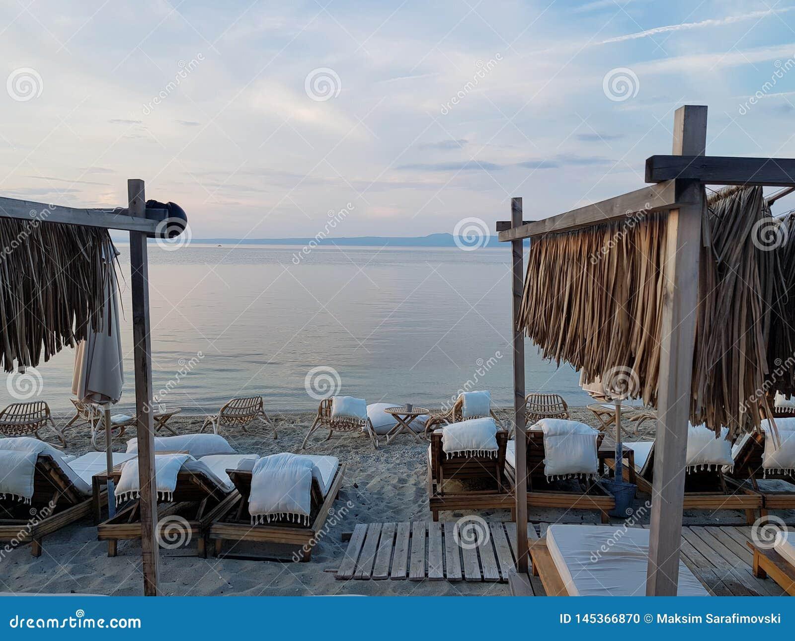 Sedie e letti bianchi sulla costa vicino al bello mare blu