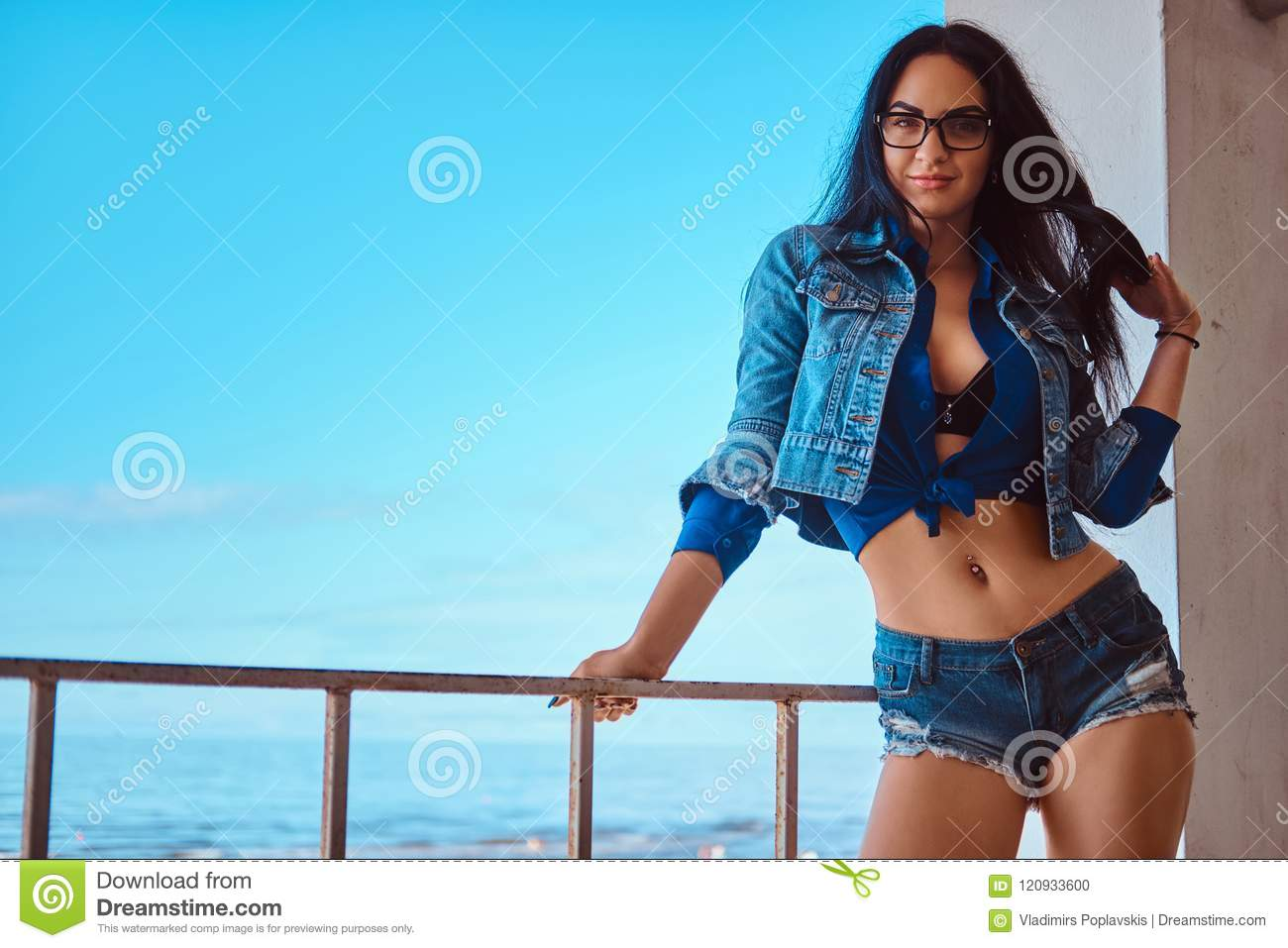 Seductive Brunette Girl Wearing Short Shorts And Jeans Jacket Posing