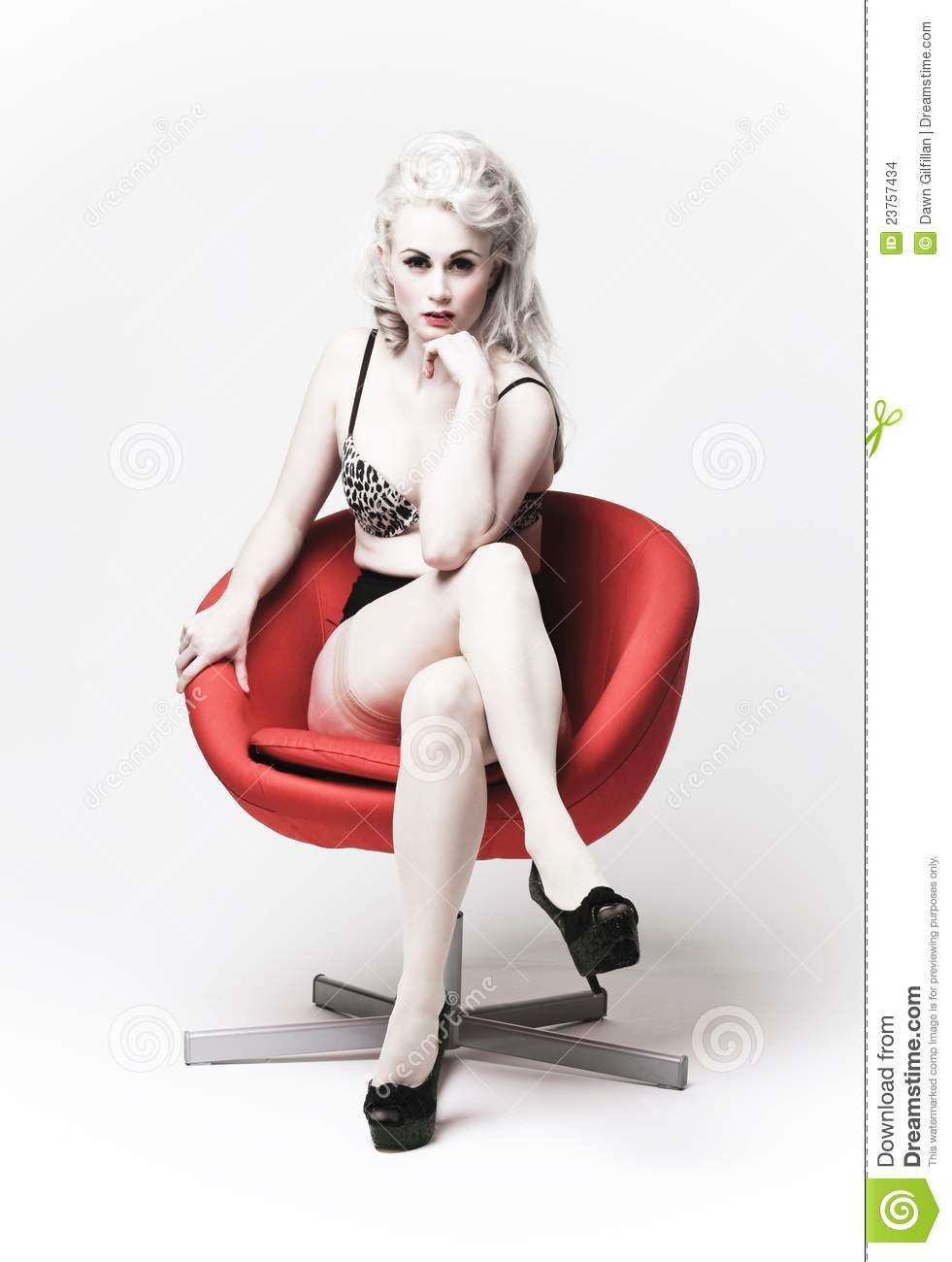 Seductive Woman In A Red Chair Stock Images