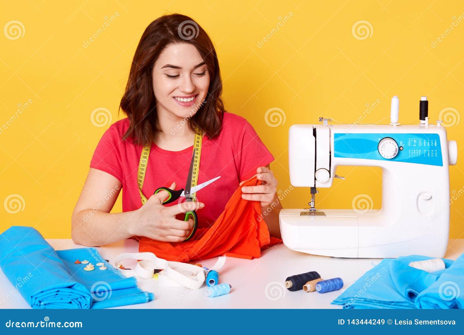 Seduta attraente del sarto della cucitrice della donna attable con la macchina per cucire sul fondo giallo in studio Il giovane s