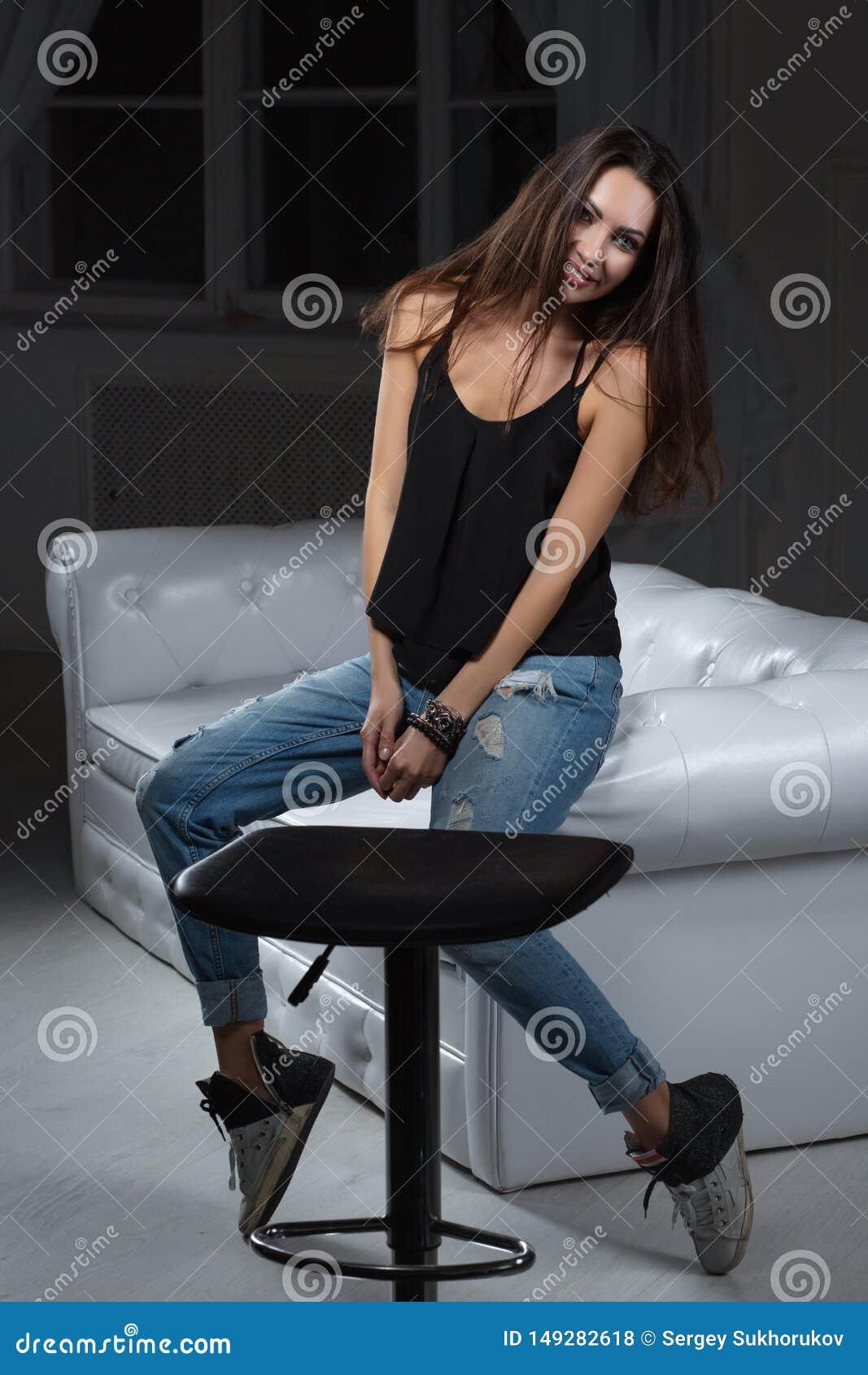 Seduta di posa castana di fascino su un sofà