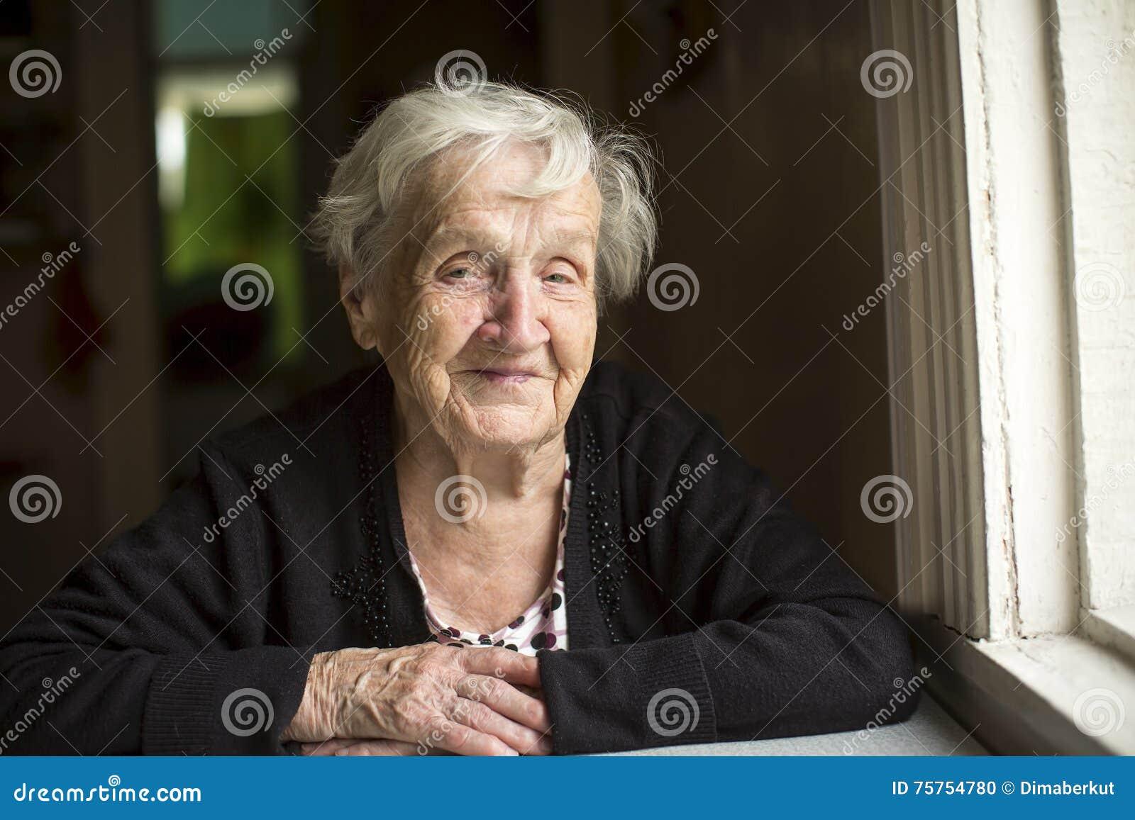 Seduta sorridente della donna anziana alla tavola felice fotografia stock immagine 75754780 - Alla tavola della longevita ...