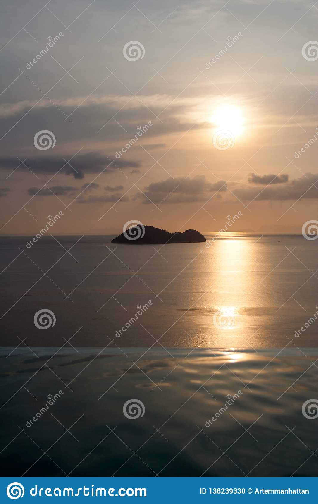 Seeinsel auf den Skylinen hinter Unendlichkeitspool unter schönem Sonnenunterganghimmel