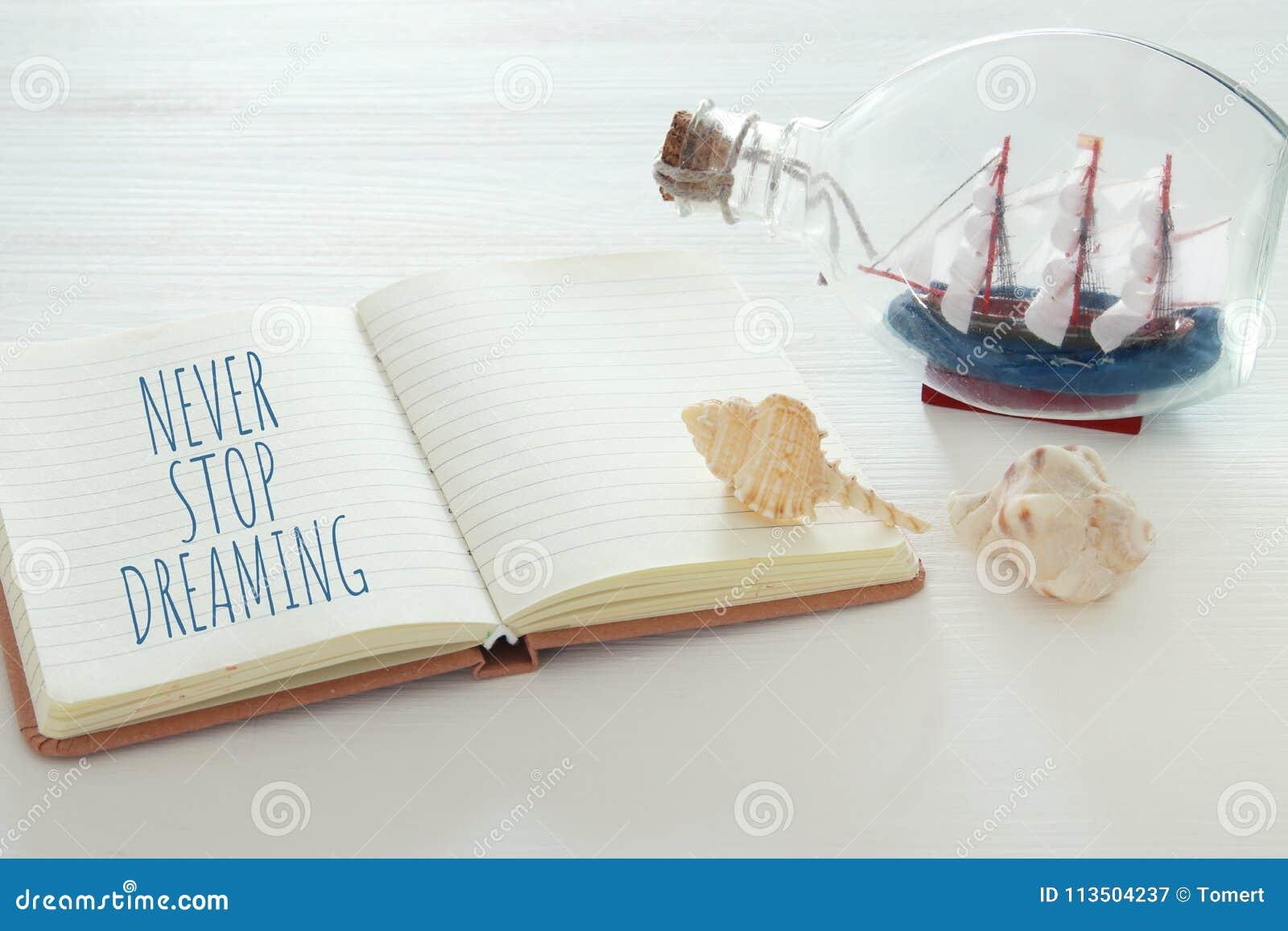 Seekonzeptbild mit Segelboot in der Flasche und in der Anmerkung: HÖREN SIE NIE AUF ZU TRÄUMEN