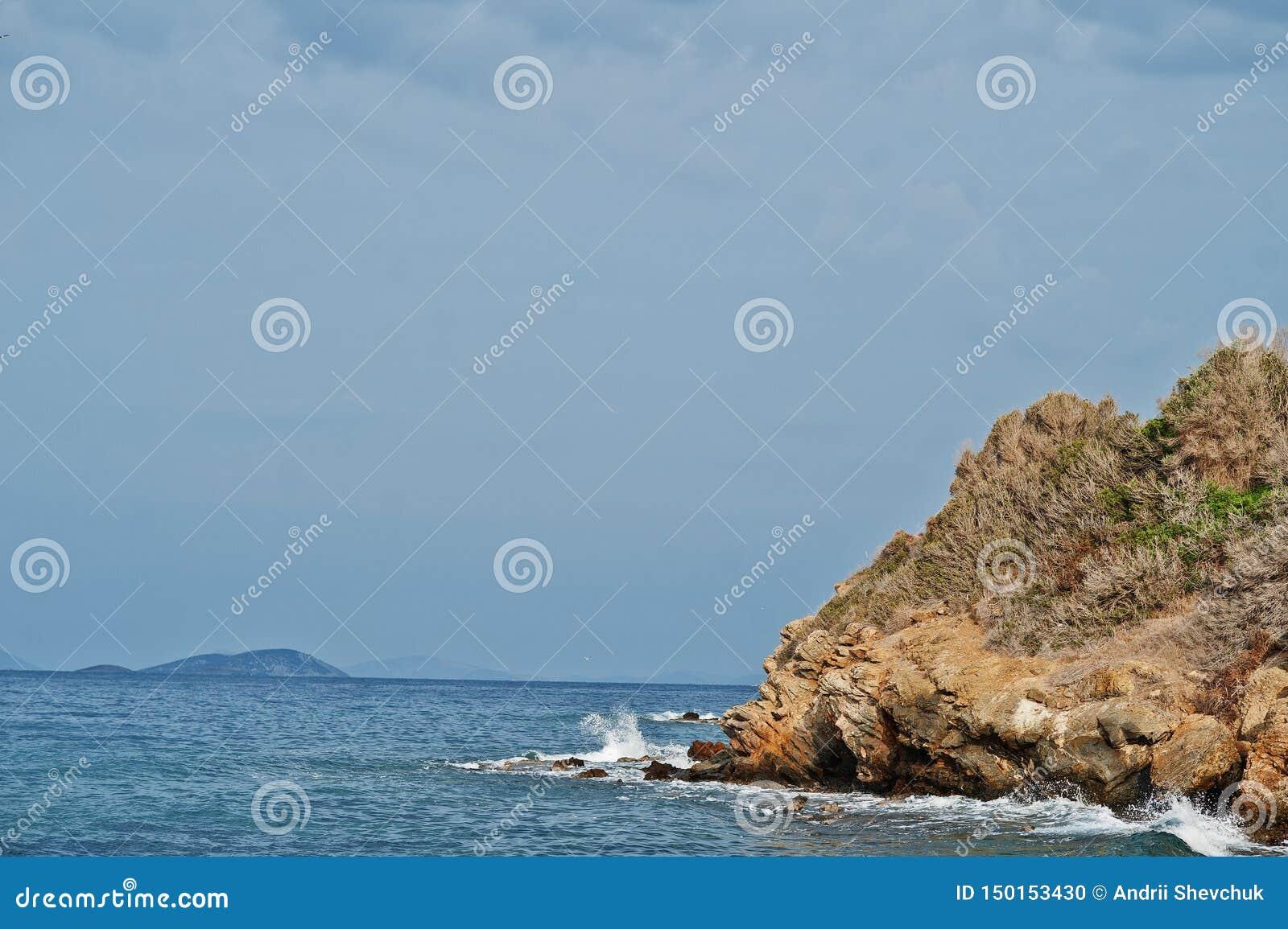 Seewellenbrecher auf Strandfelsen gestalten landschaftlich Meereswellen stoßen zusammen und spritzen auf Felsen bei Bodrum, die T