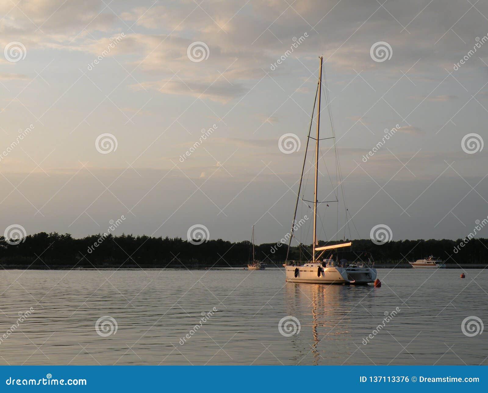 Segelboote und Yachten schwimmen auf eine ruhige Oberfläche von theAdriatic Meer, Kroatien, Europa Im Hintergrund die Küste mit m