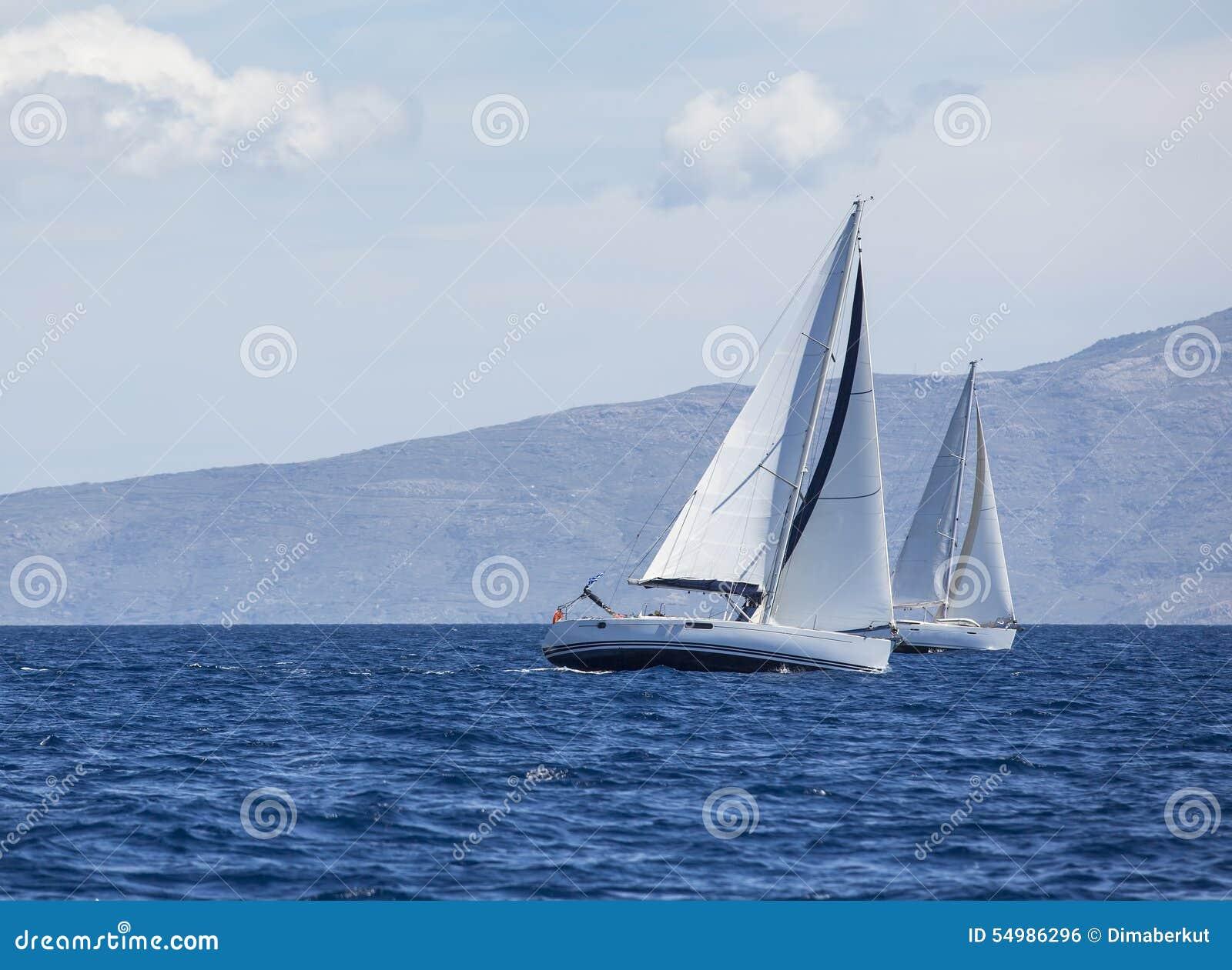 Segla i vinden till och med vågorna på det Aegean havet i Grekland Rader av lyxiga yachter på marinaskeppsdockan