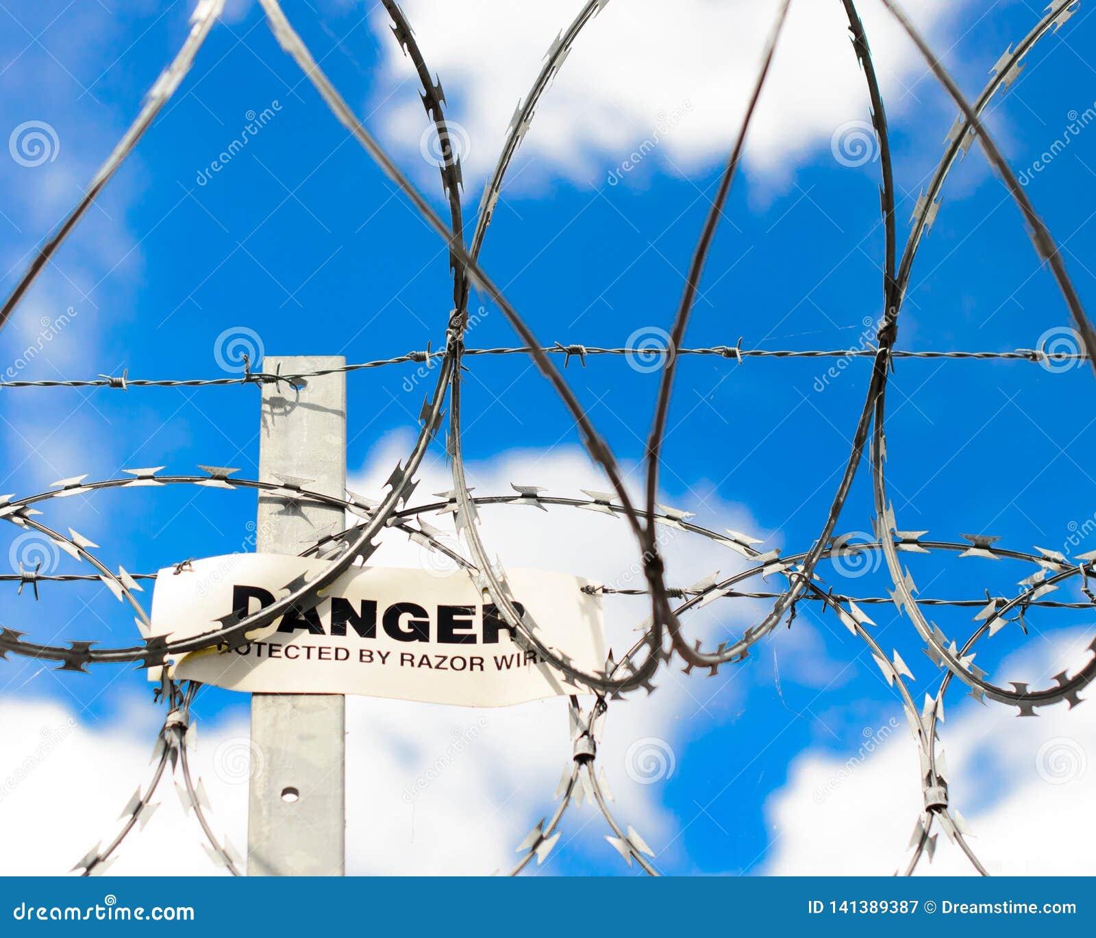 Segnale di pericolo e filo spinato