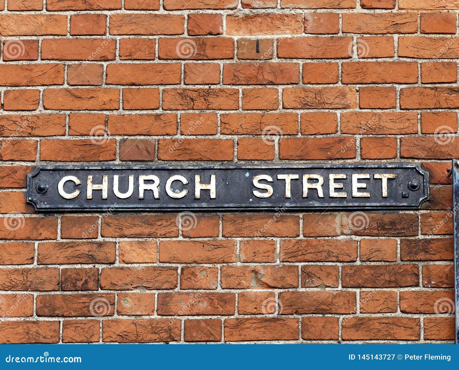 Segnale stradale della chiesa allegato al muro di mattoni
