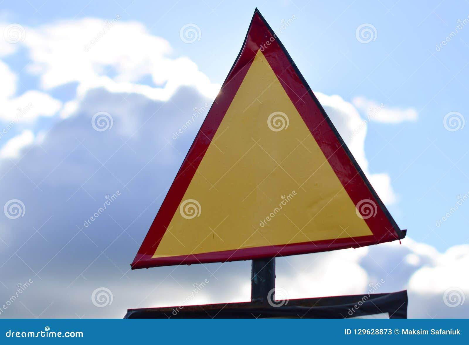 Segnale stradale triangolare su un fondo del cielo