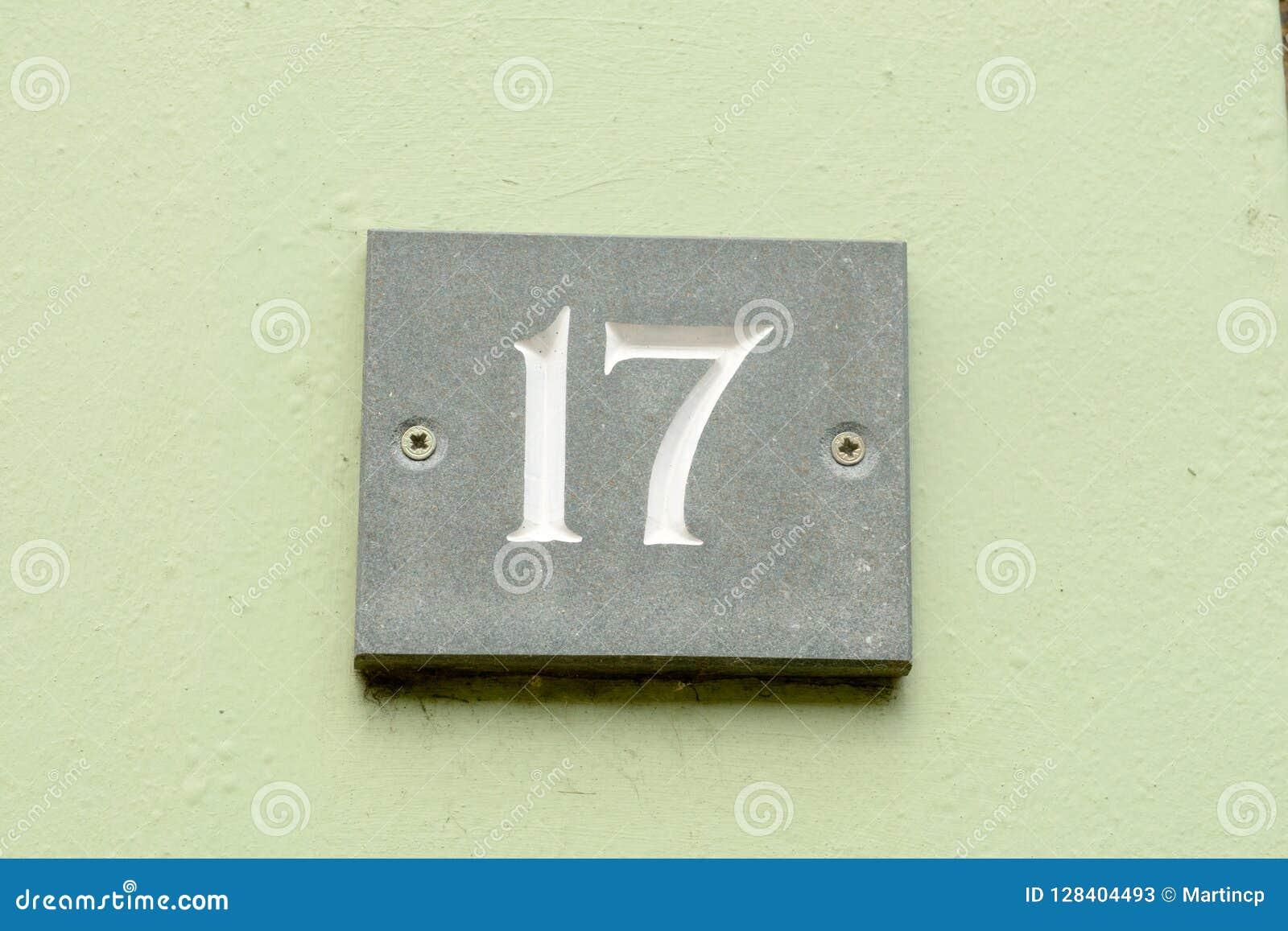 Segno del numero civico 17 sulla parete dipinta verde immagine stock