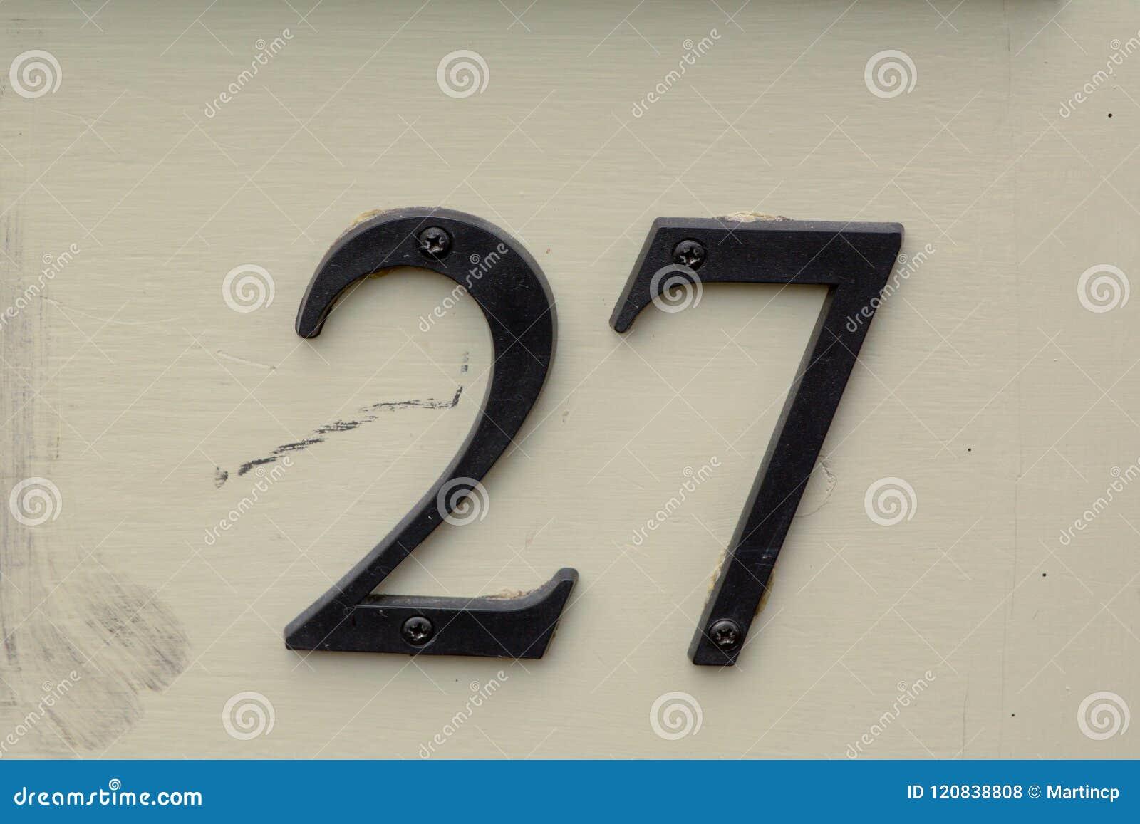 Segno del numero civico sulla porta di legno fotografia stock