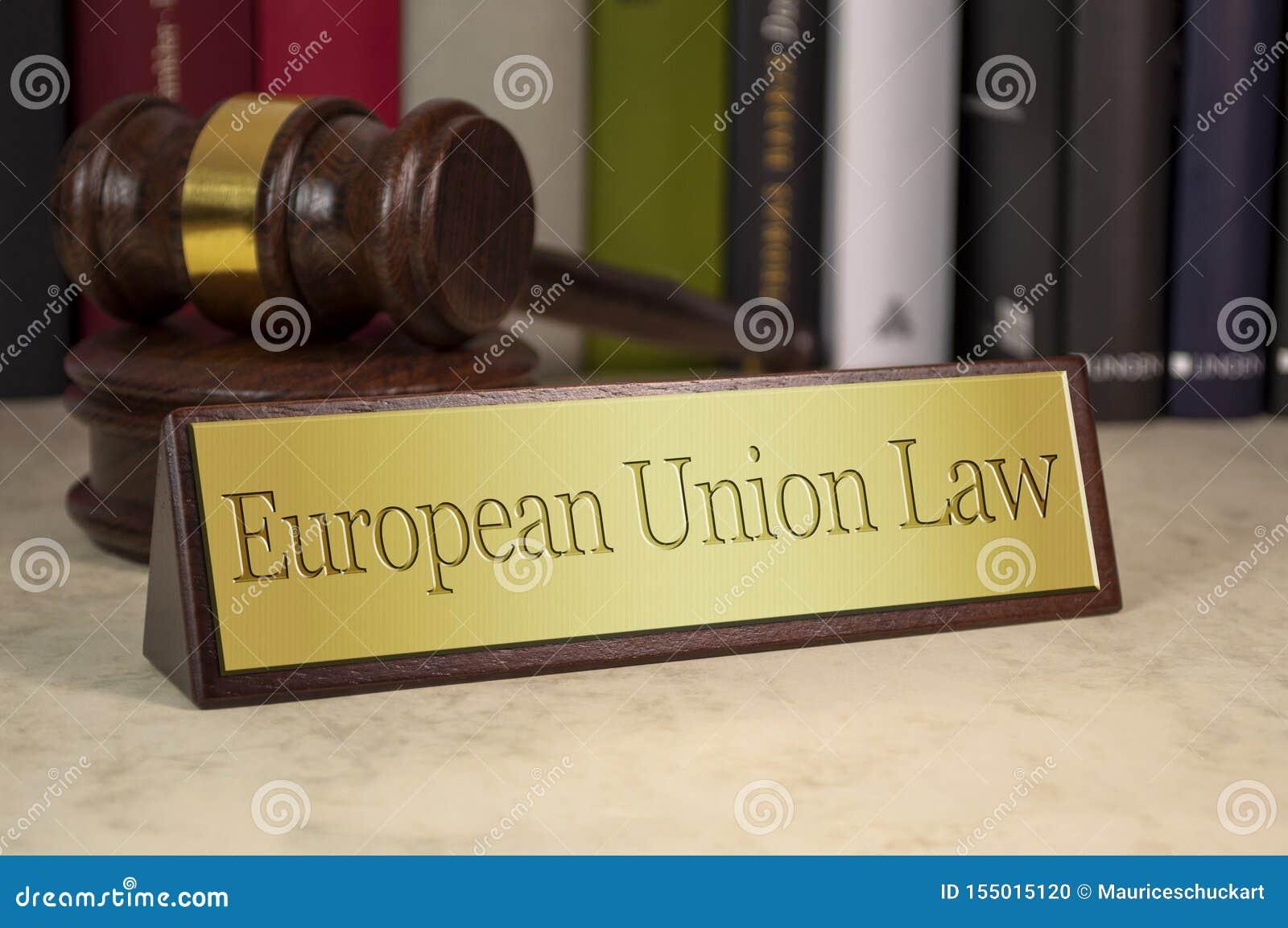 Segno dorato con il martelletto su uno scrittorio con legge dell Unione Europea