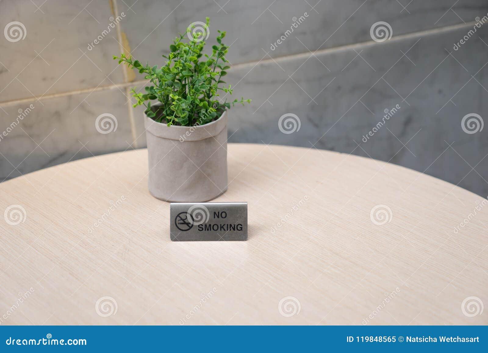 Segno non fumatori sulla tavola di legno leggera con un vaso di verde falso t