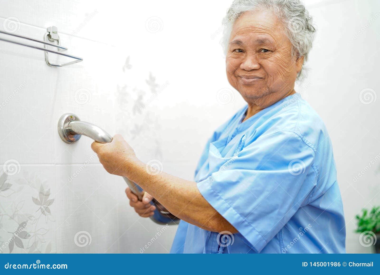 Seguran?a paciente asi?tica do punho do banheiro do toalete do uso da mulher superior ou idosa da senhora idosa na divis?o de hos