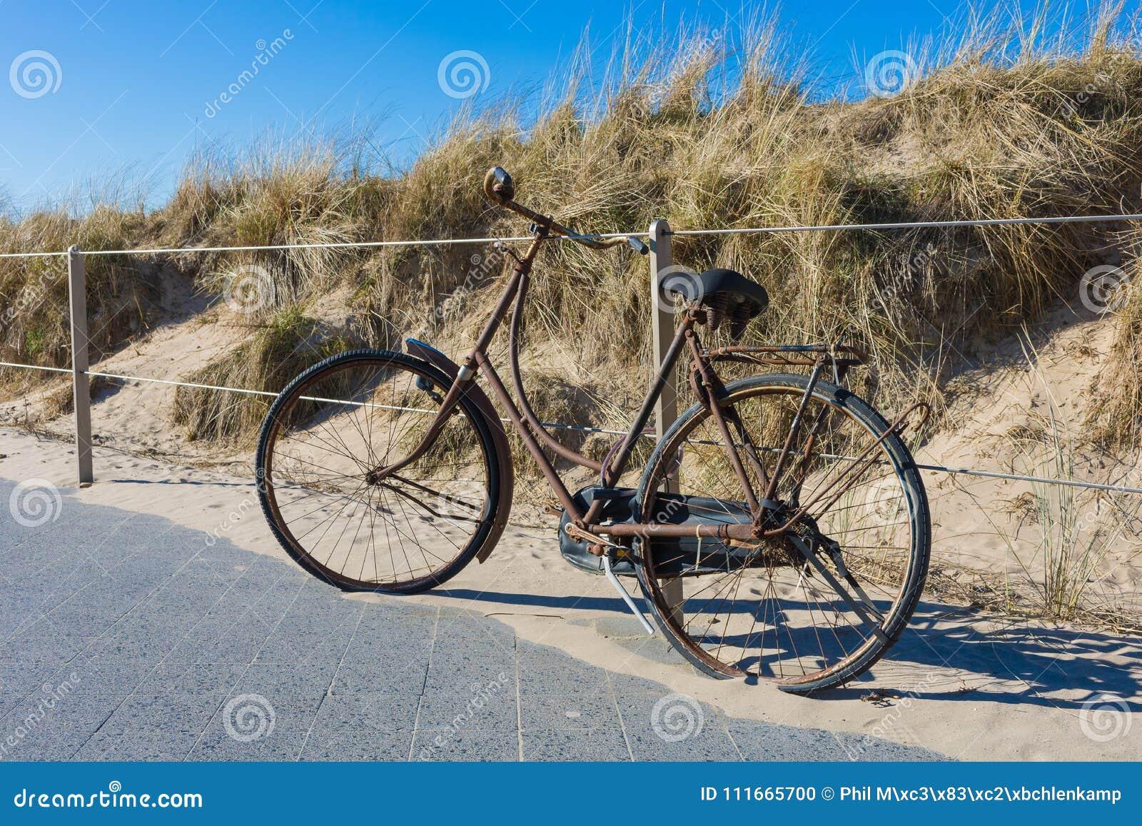 Sehr altes und rostiges Fahrrad, verschlossen zu einem modernen Stahlzaun
