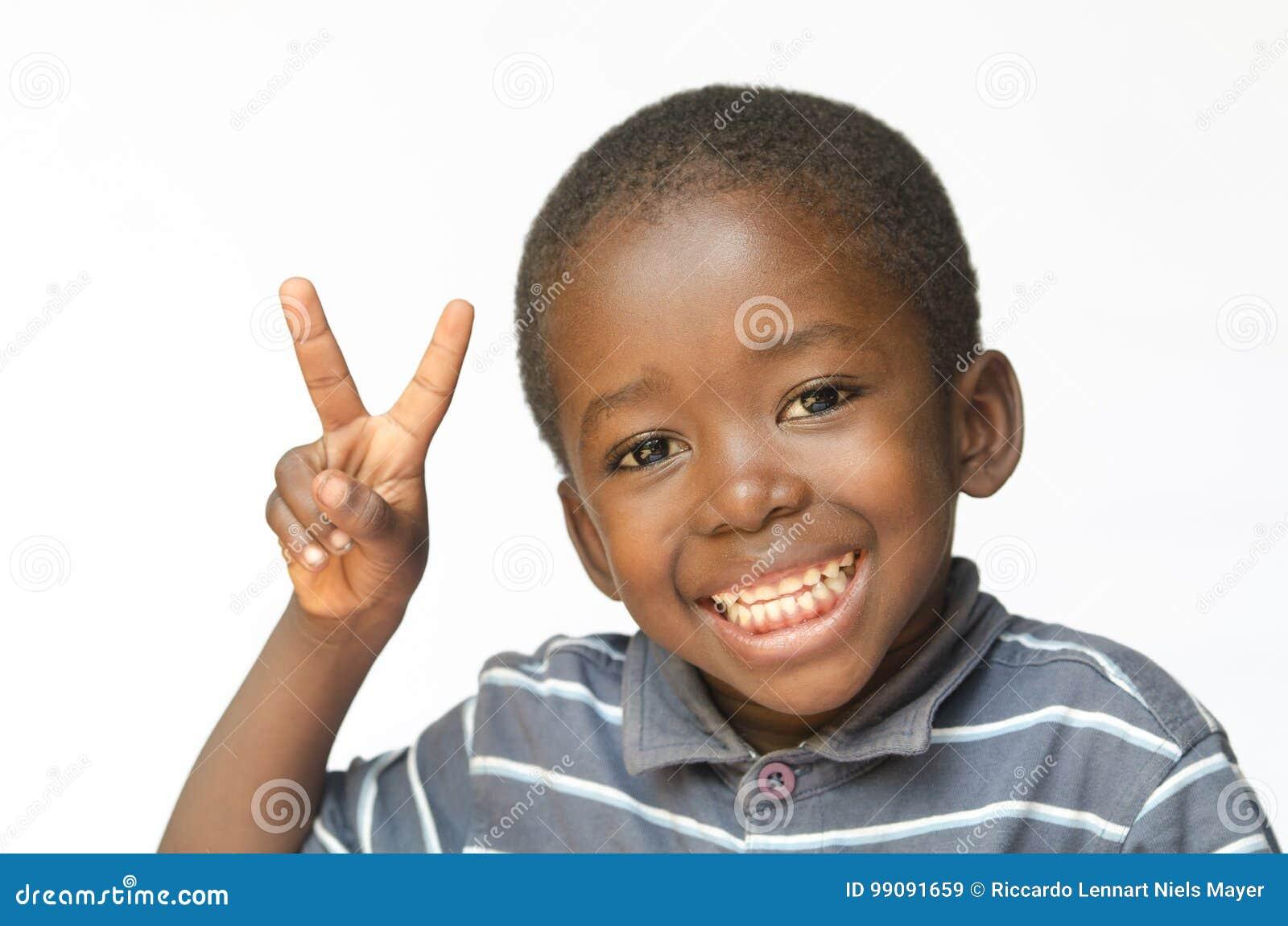 Sehr glücklicher afrikanischer schwarzer Junge, der Friedenszeichen für Lächelnfrieden afrikanischer Ethnie Afrikas enormen für d
