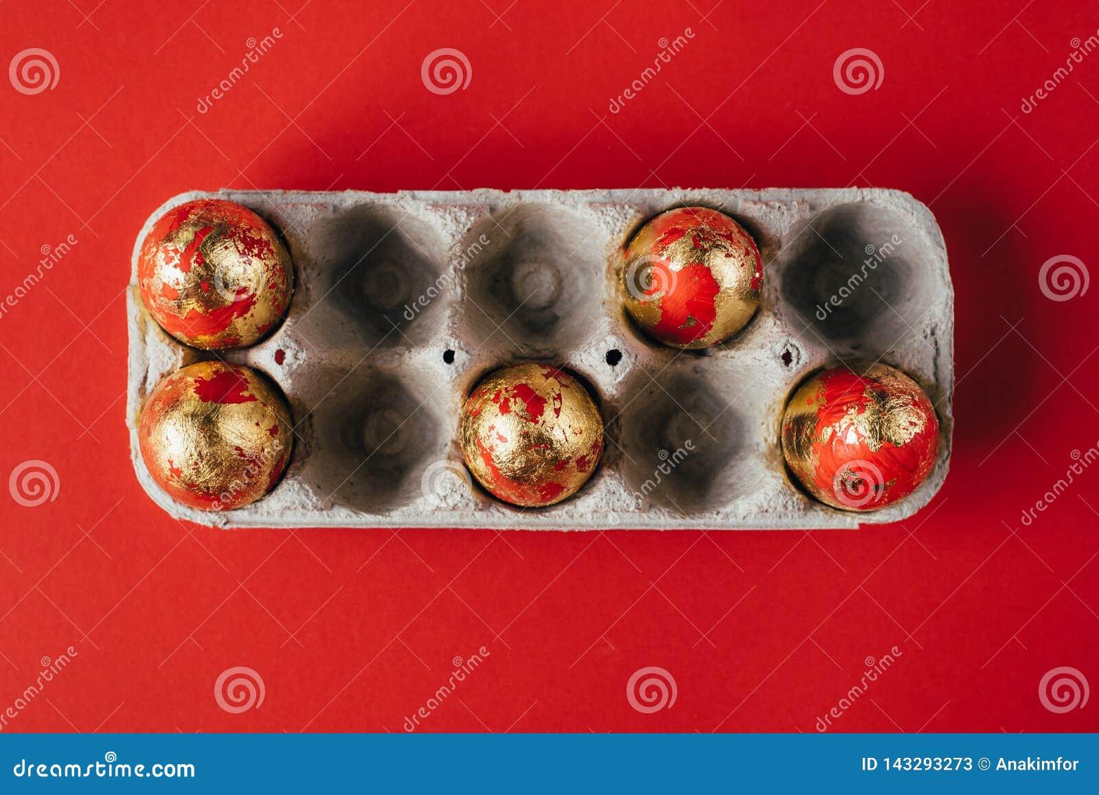 Sei colorate dorate e decorato con le uova di Pasqua delle scintille in uovo-scatola del cartone