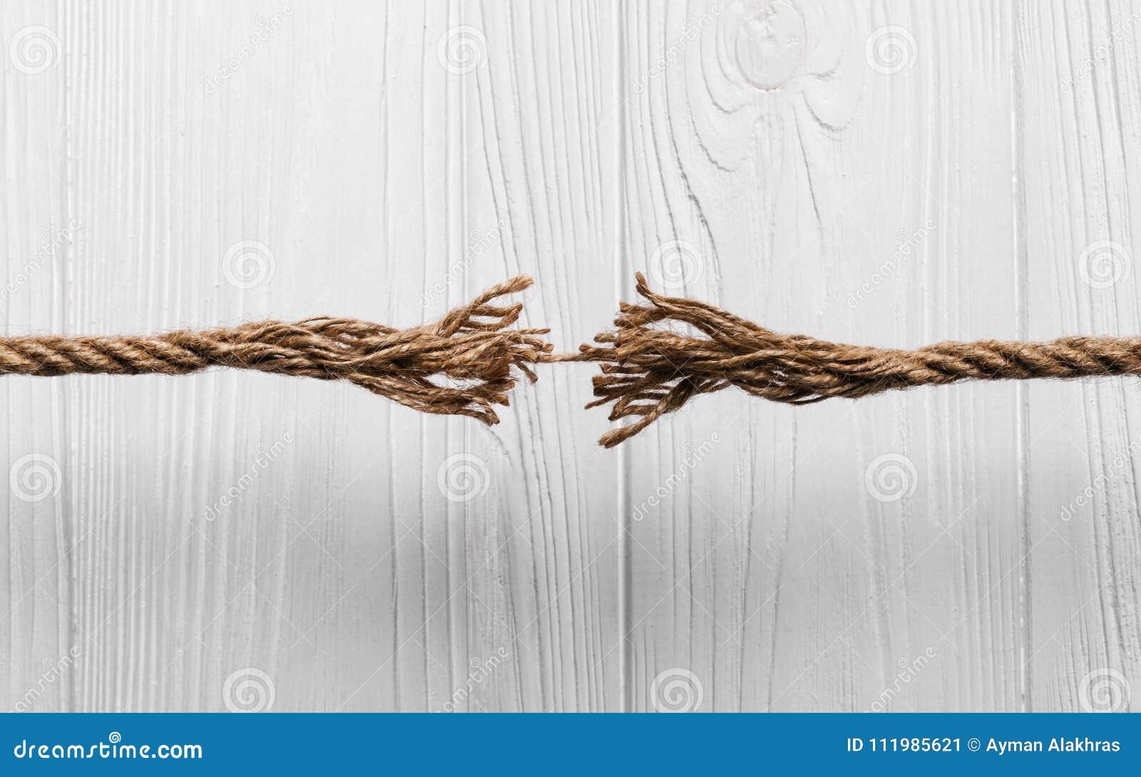 Seil franste ungefähr aus, um auf hölzernem Hintergrund zu brechen
