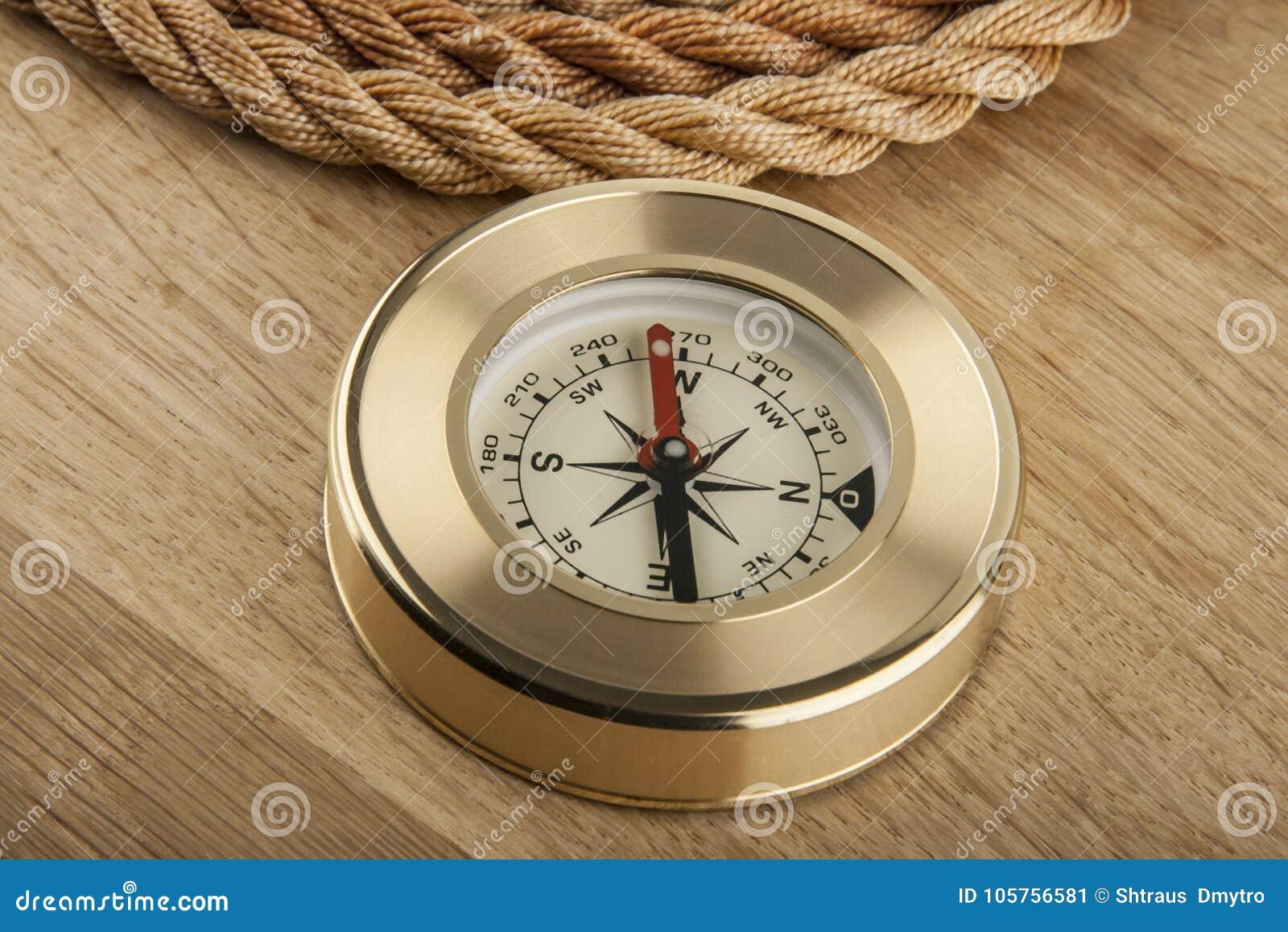 Seil und Kompass auf einem hölzernen