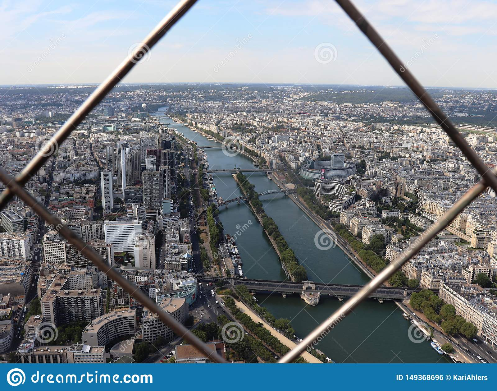 The Seine and Paris through the bars of the Eiffel Tower